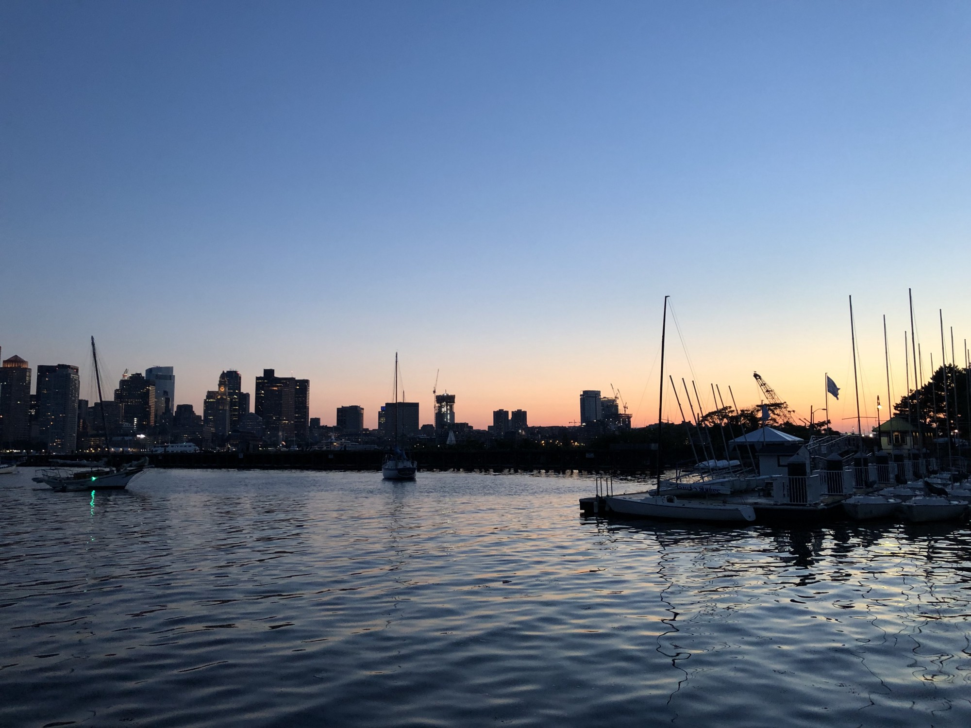 The Boston Harbor at dusk with buildings in the background and boats in the foreground.
