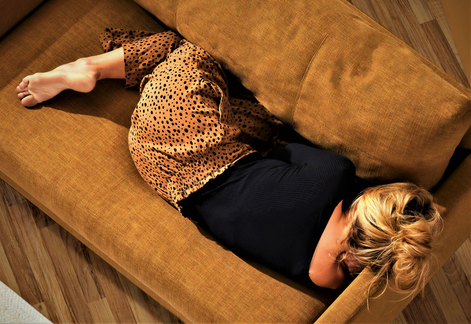 girl with blond hair wearing black top curled up on tan couch