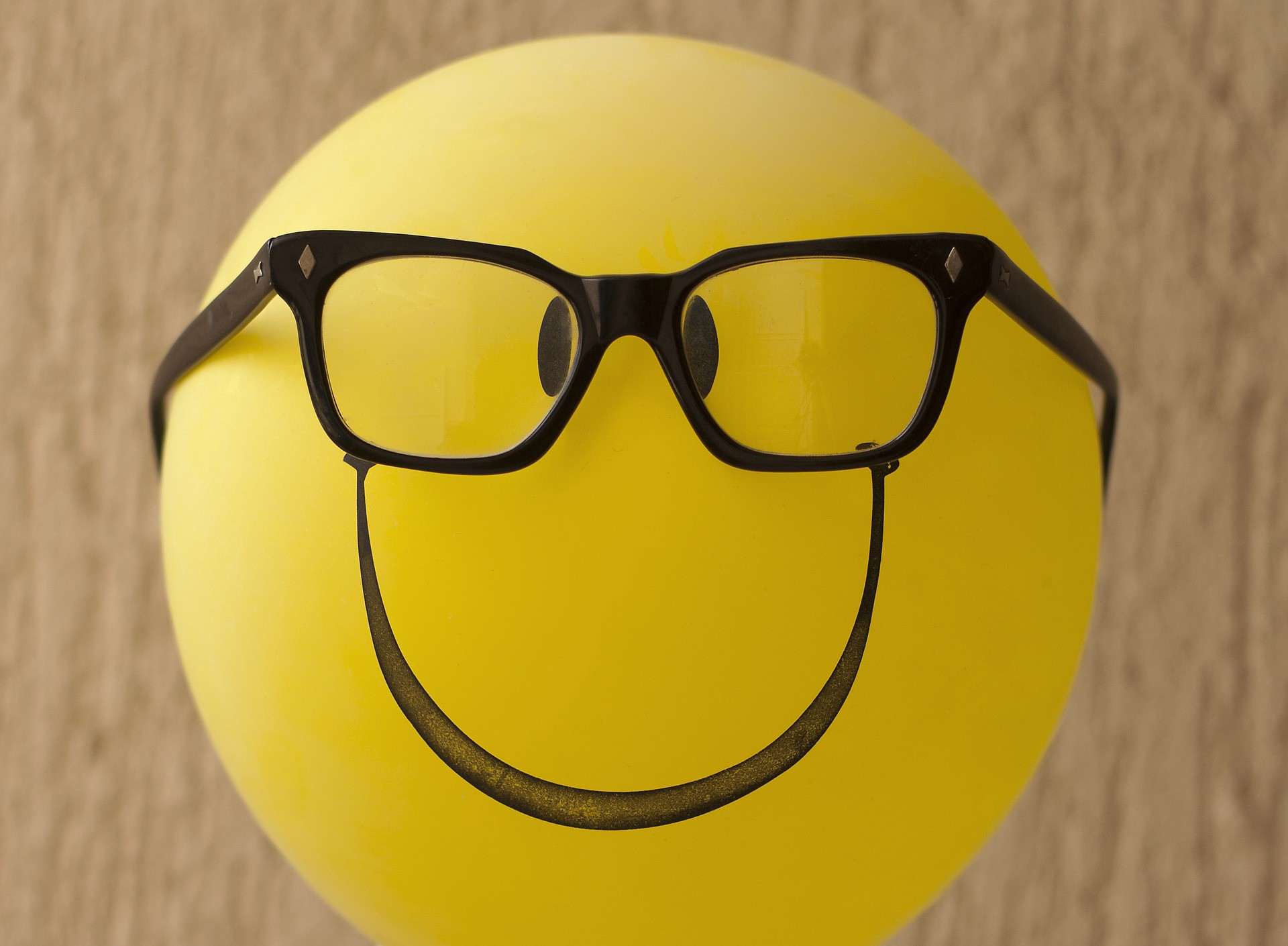 A yellow balloon with eyes and nose drawn on with marker and a pair of real glasses.