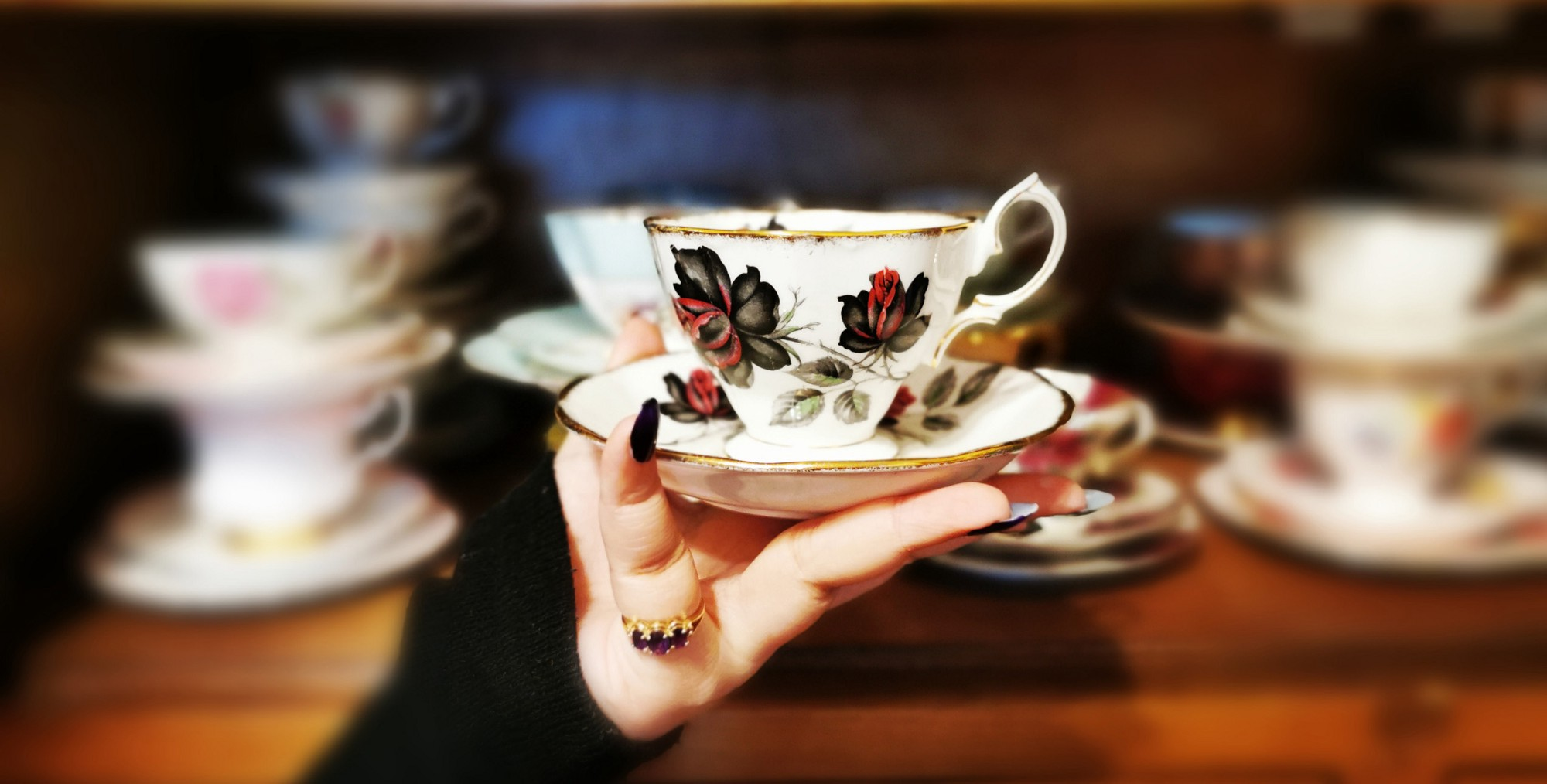 Author holds vintage Royal Albert Masquerade Tea Cup in hand.