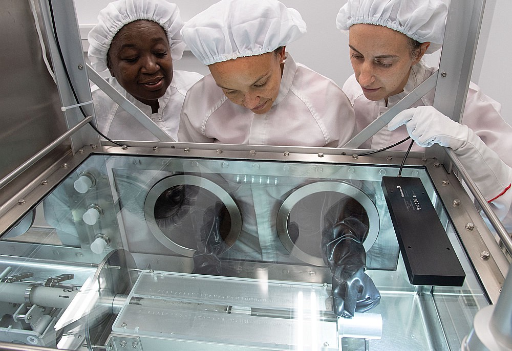 Three NASA researchers, all women, examine a sample of lunar material brought to Earth by the Apollo astronauts.