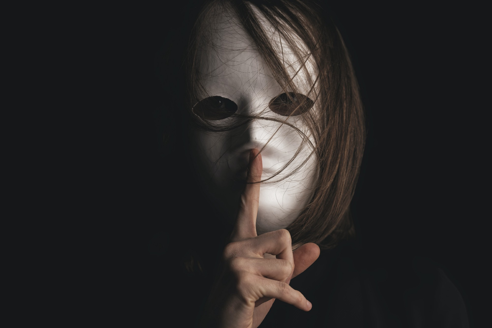 Woman with white full-face mask holding a finger up to her lips.