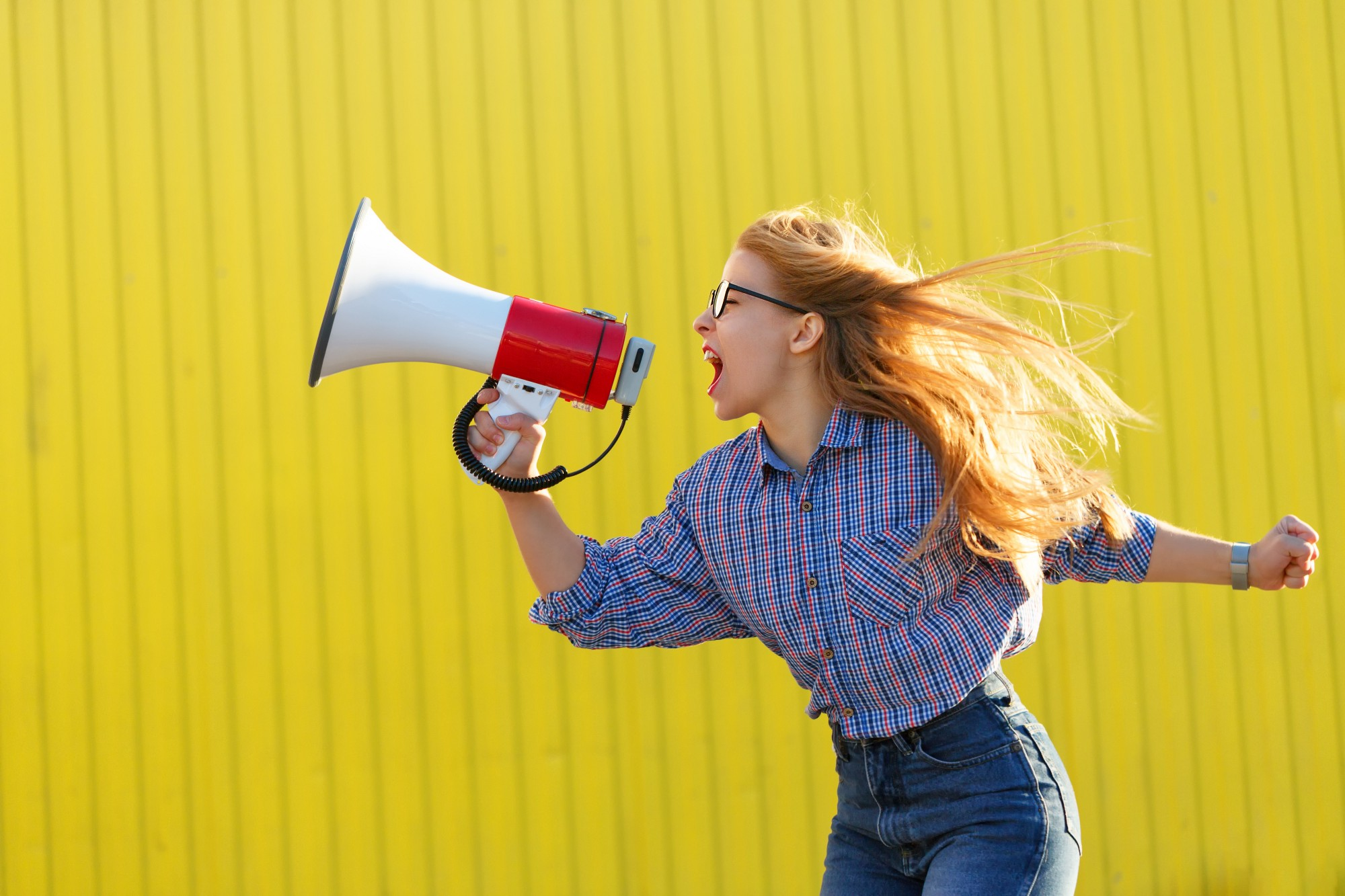 A person with long hair screaming into a megaphone.