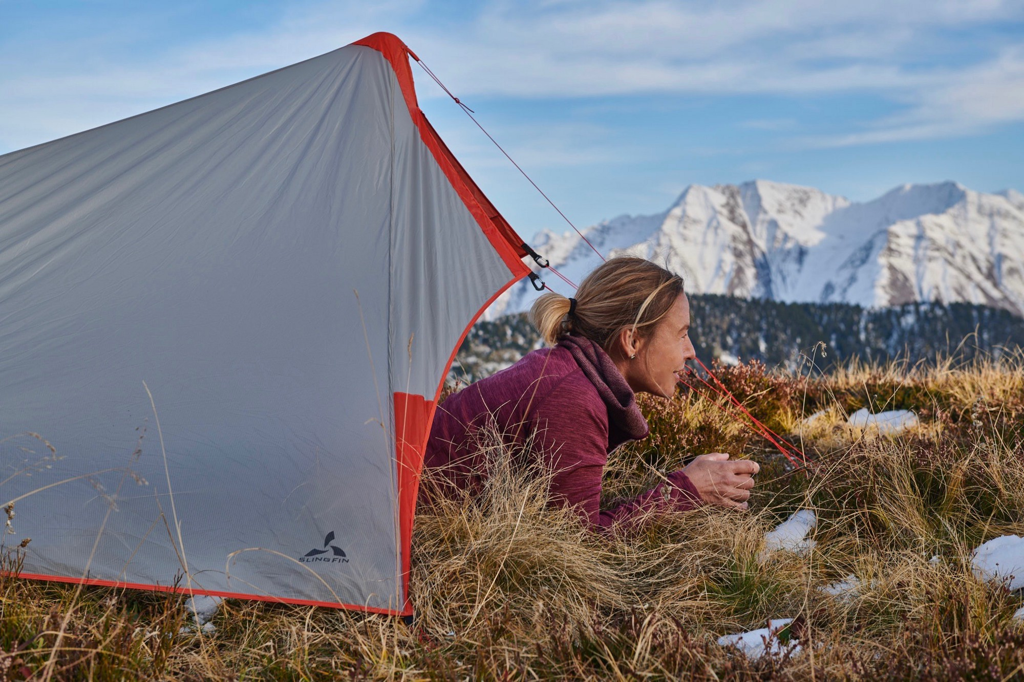 Women looking out from a tent in the Swiss mountains.