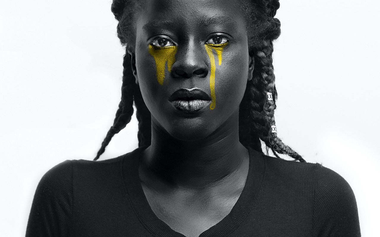 Grayscale photography of a black woman with yellow tears.