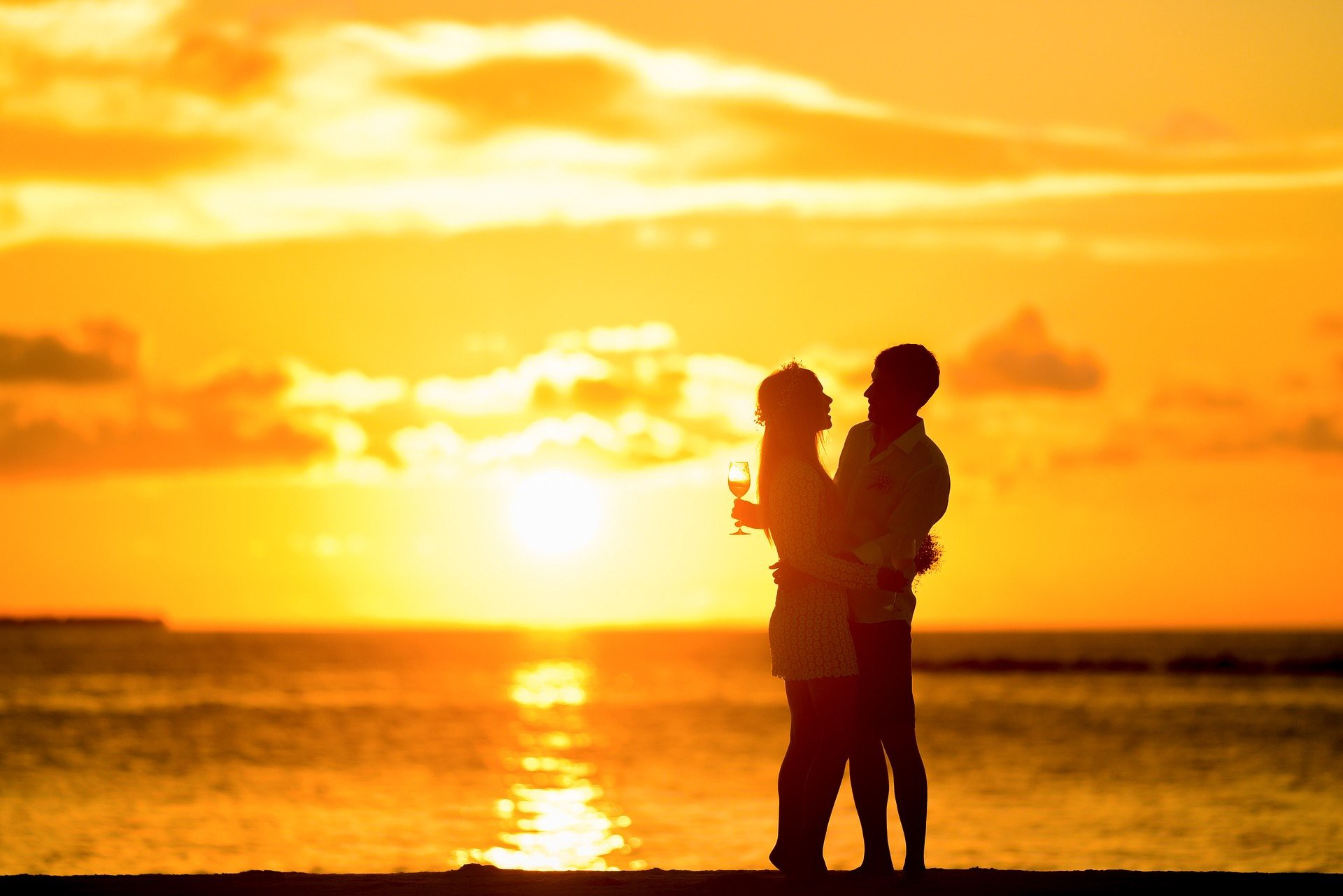Couple on the beach at sunset with arms wrapped around each other celebrating the intensity of love they feel for each other.