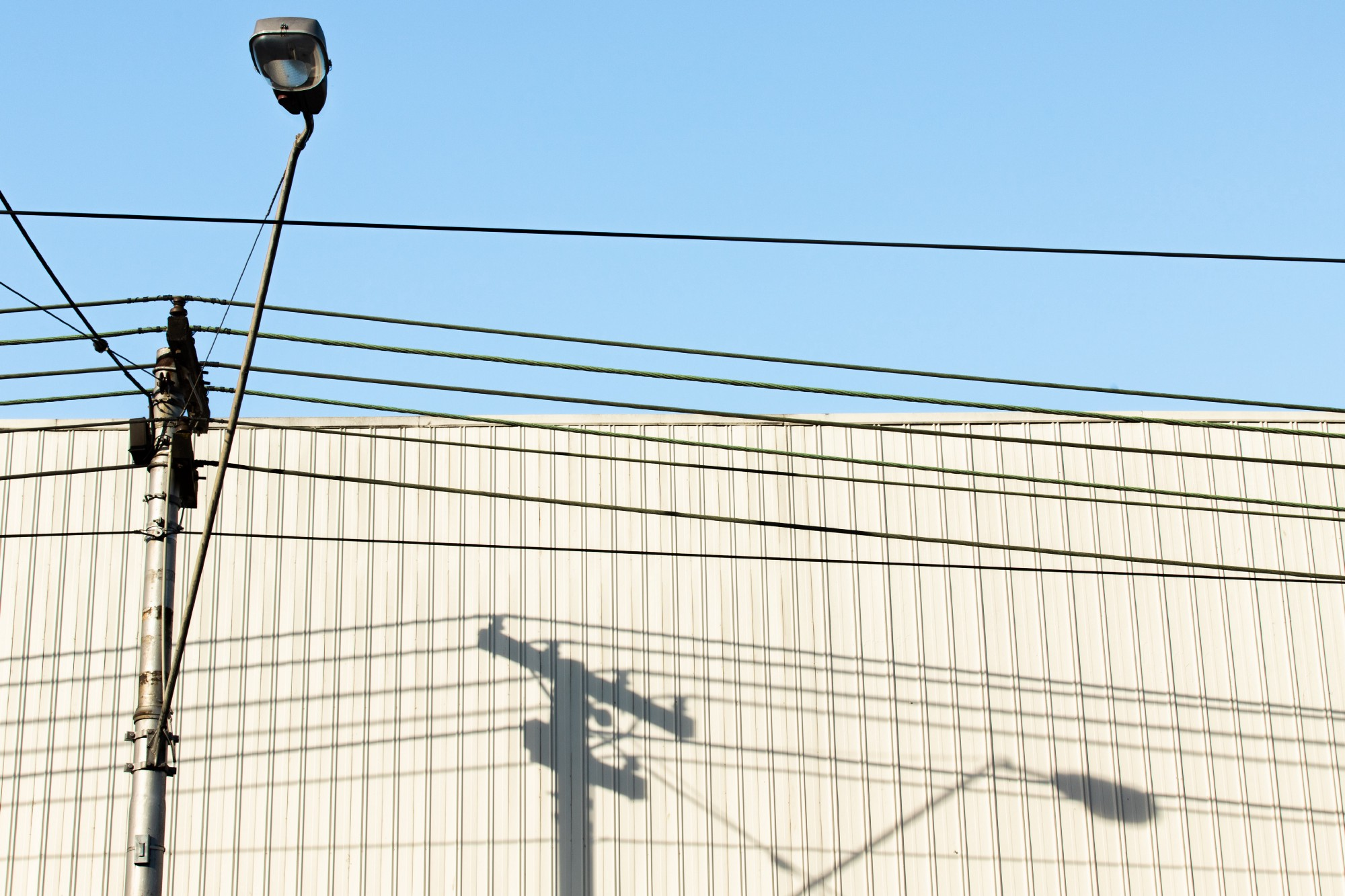A camera attached to a utility pole with wires against a beige building and blue sky.