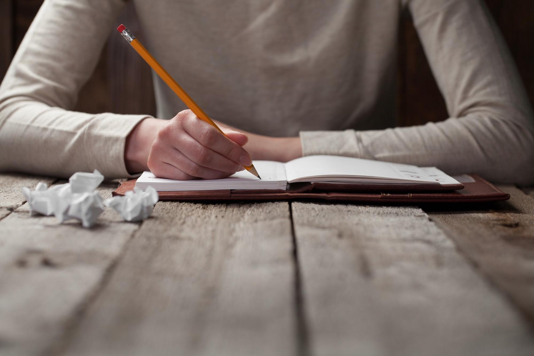 Writing with a pencil in a leather-bound notebook with crumpled drafts on a wooden table.