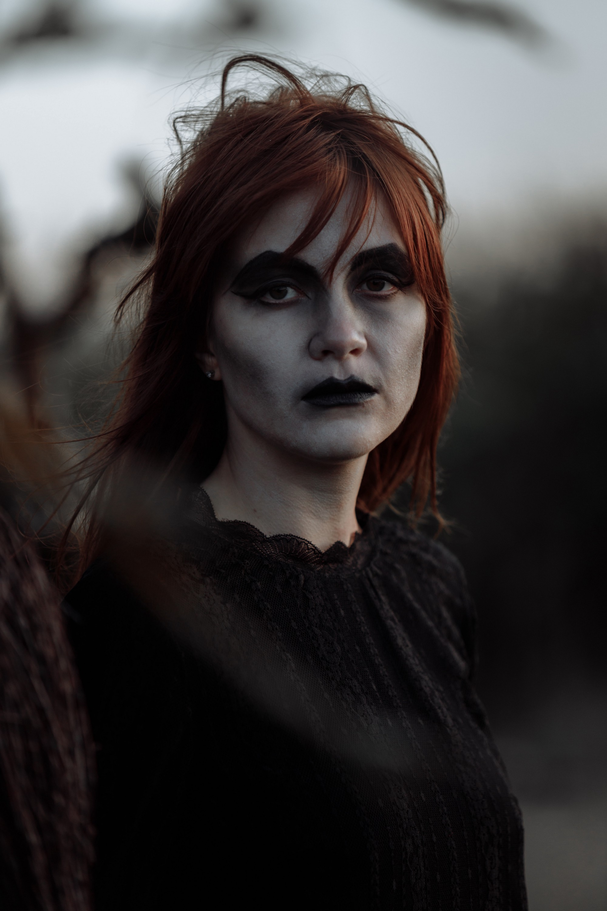 A female Zombie dressed in black with red hair.