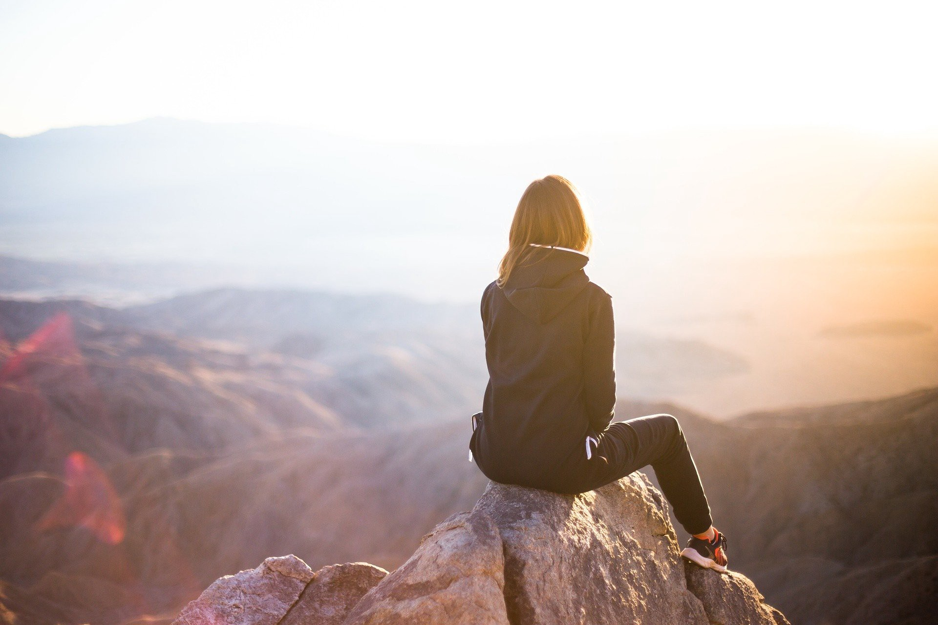 Woman sitting on a rock looking out a the view