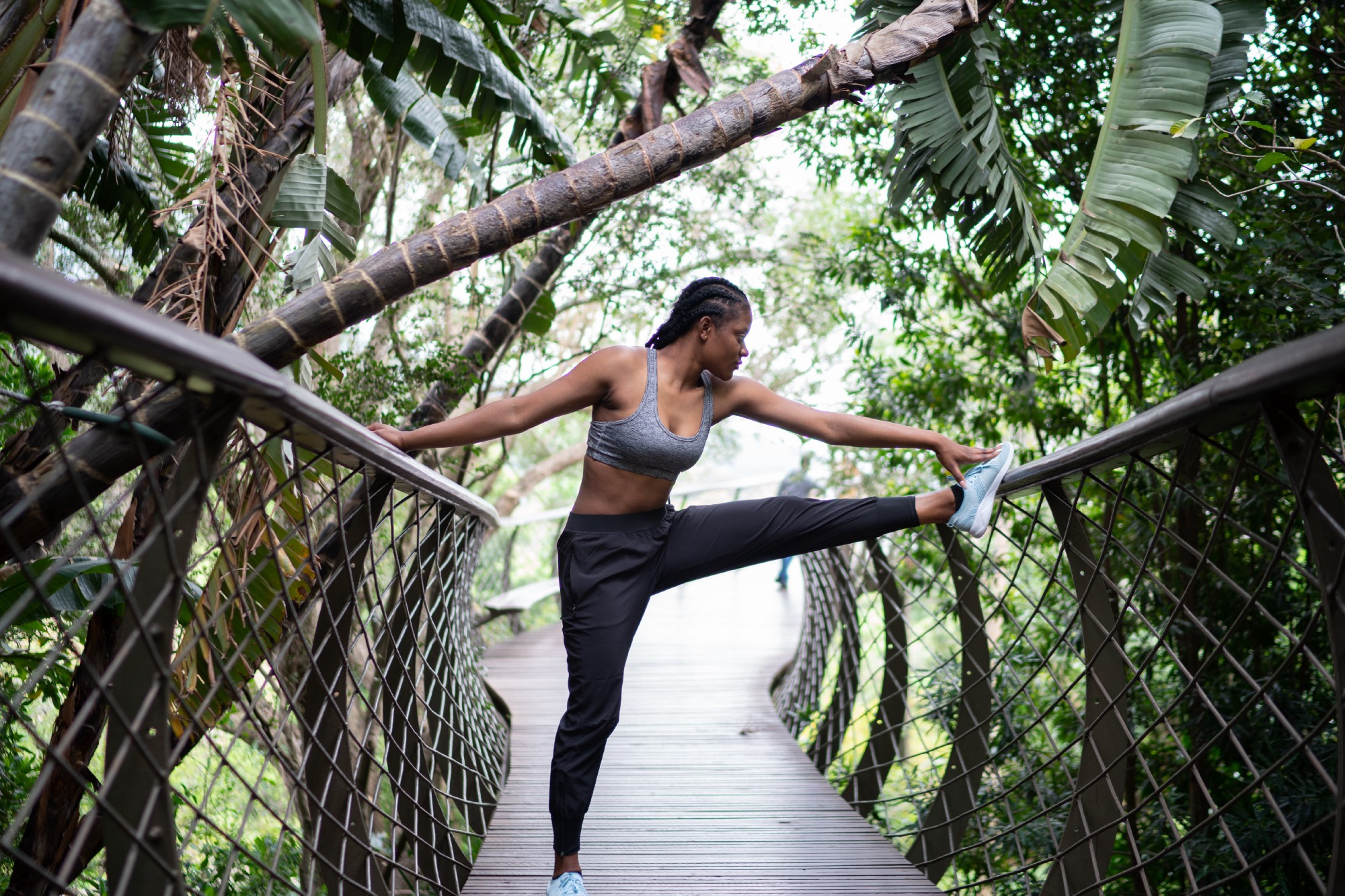 Woman stretching with leg propped up on a railing surrounded by trees