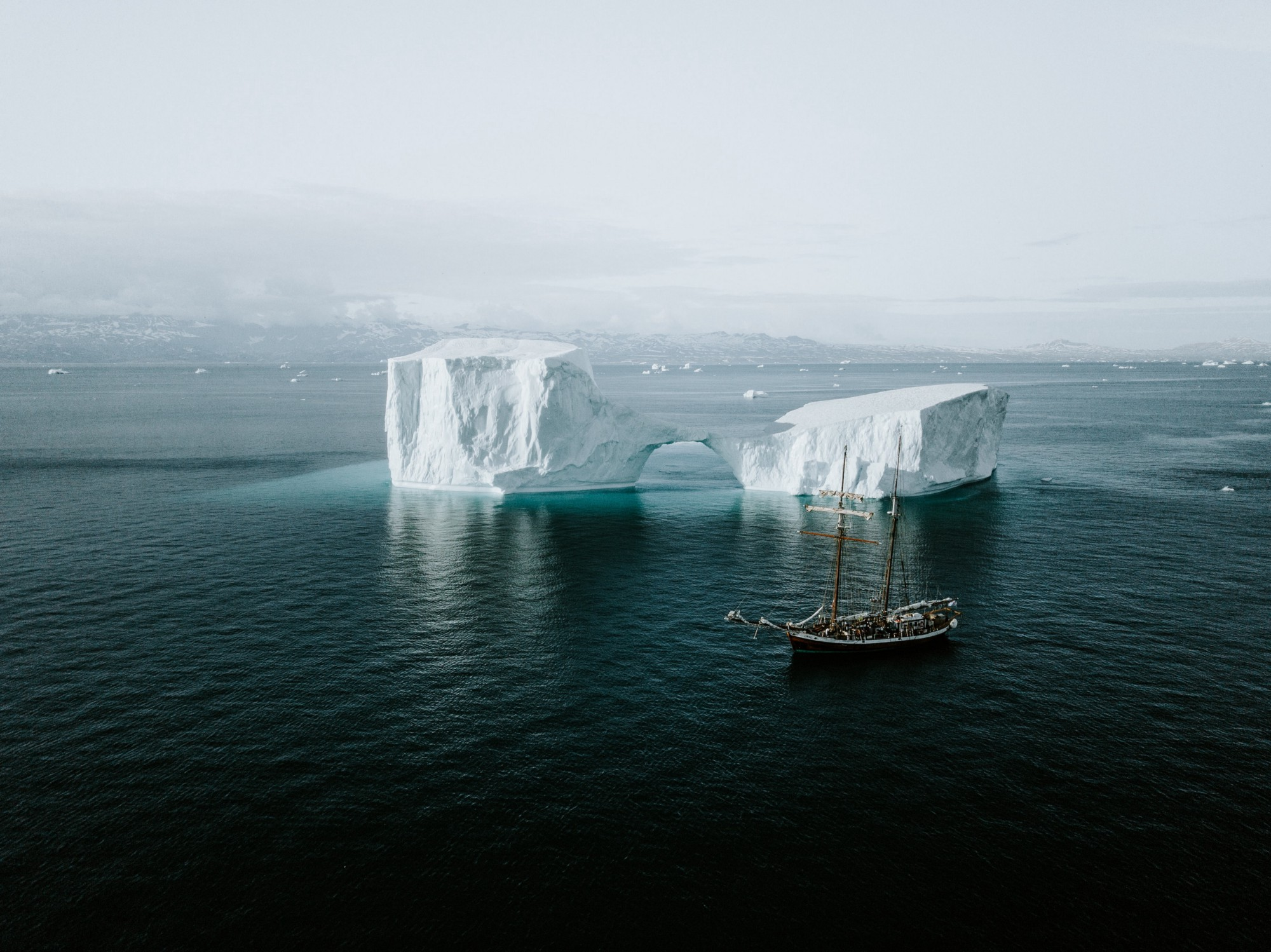 Boat floating by icebergs