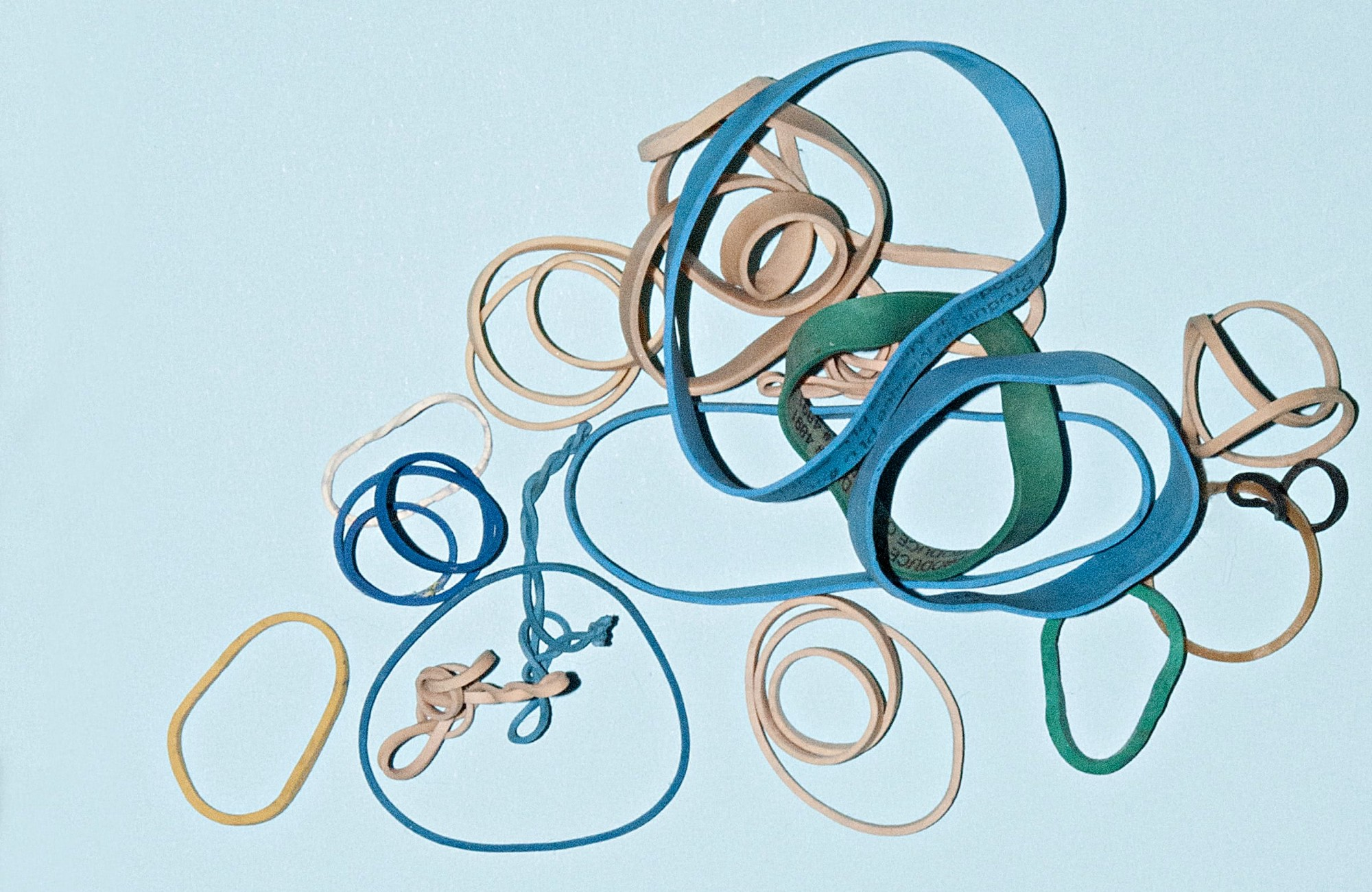 Lots of different circular rubber bands on a bright background thrown on top of each other. Some are twisted, others are nearly round.