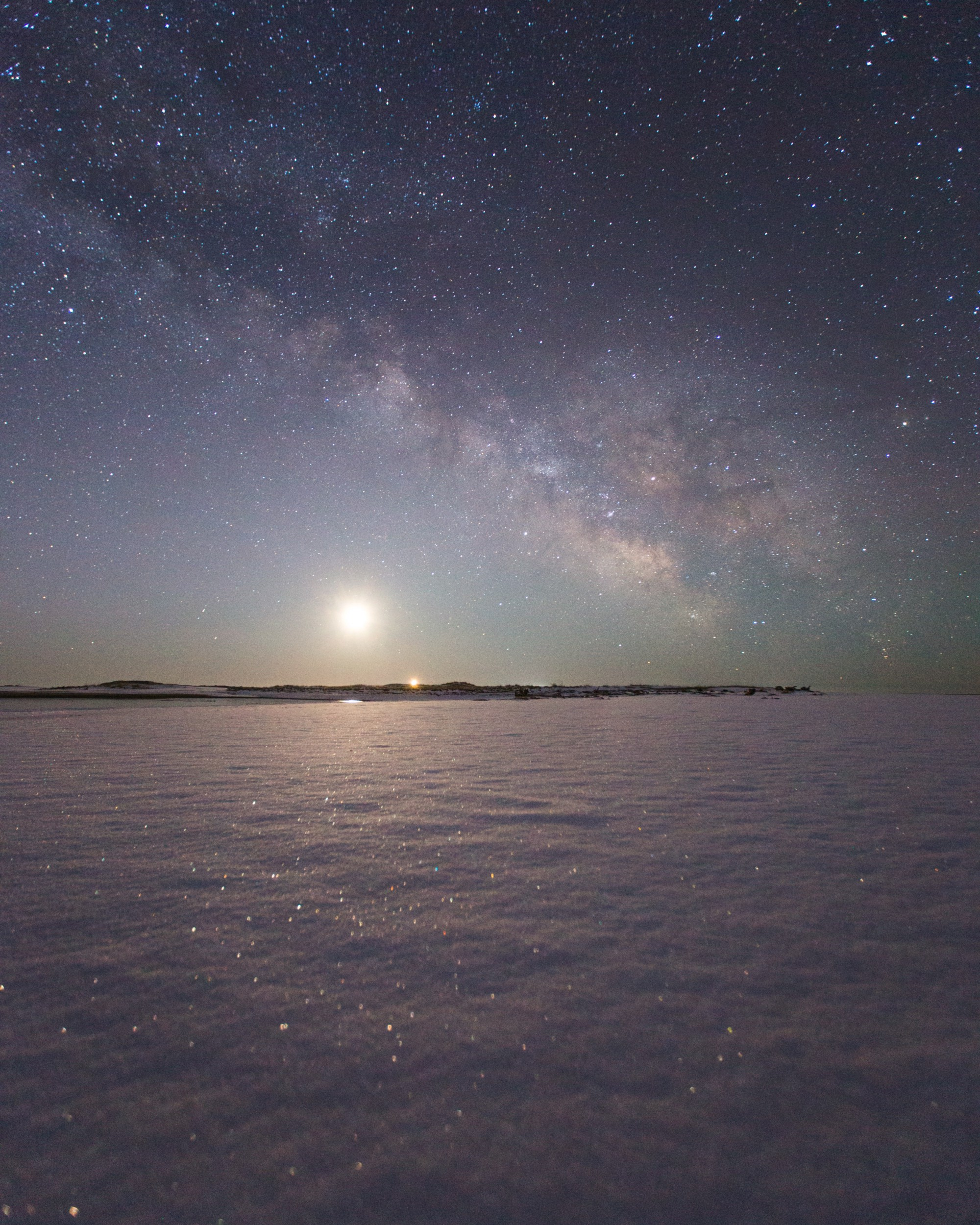 Snow-covered intertidal flats in Maine reflecting milky way and low sun