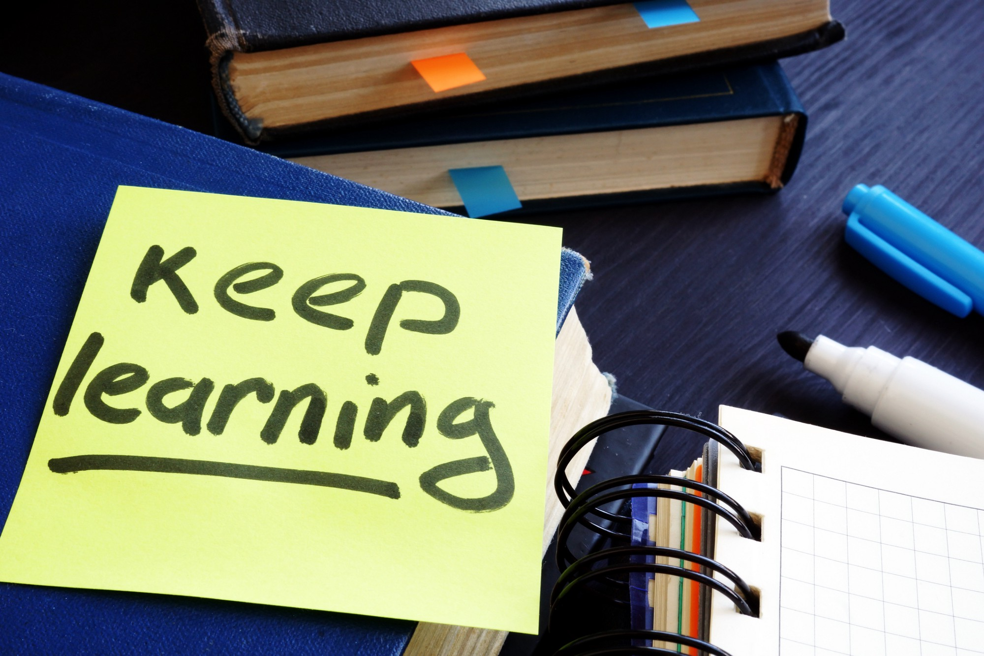 """Collection of books, notepads and pens with a post-it note on top, reading """"keep learning."""""""