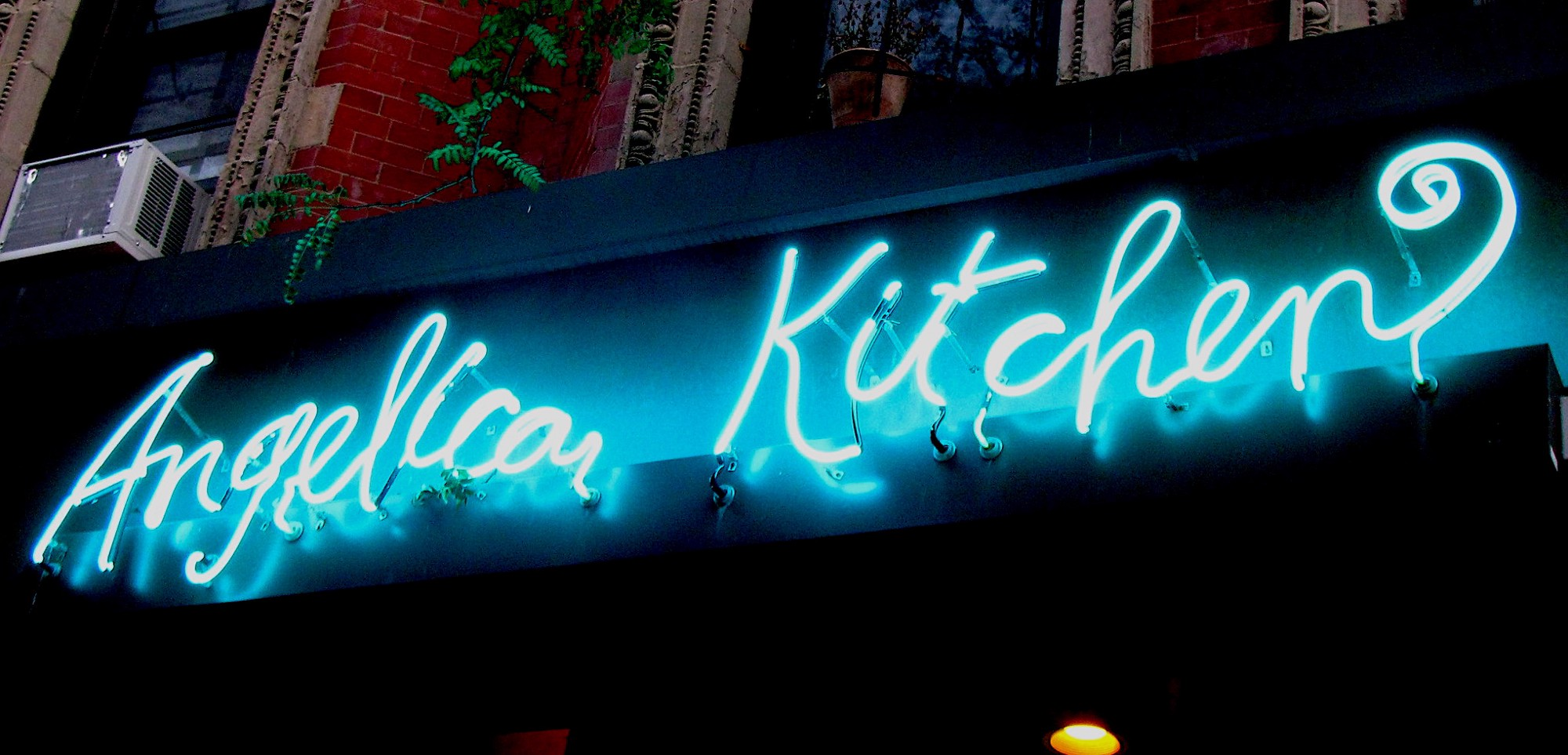 A blue neon sign reading Angelica Kitchen