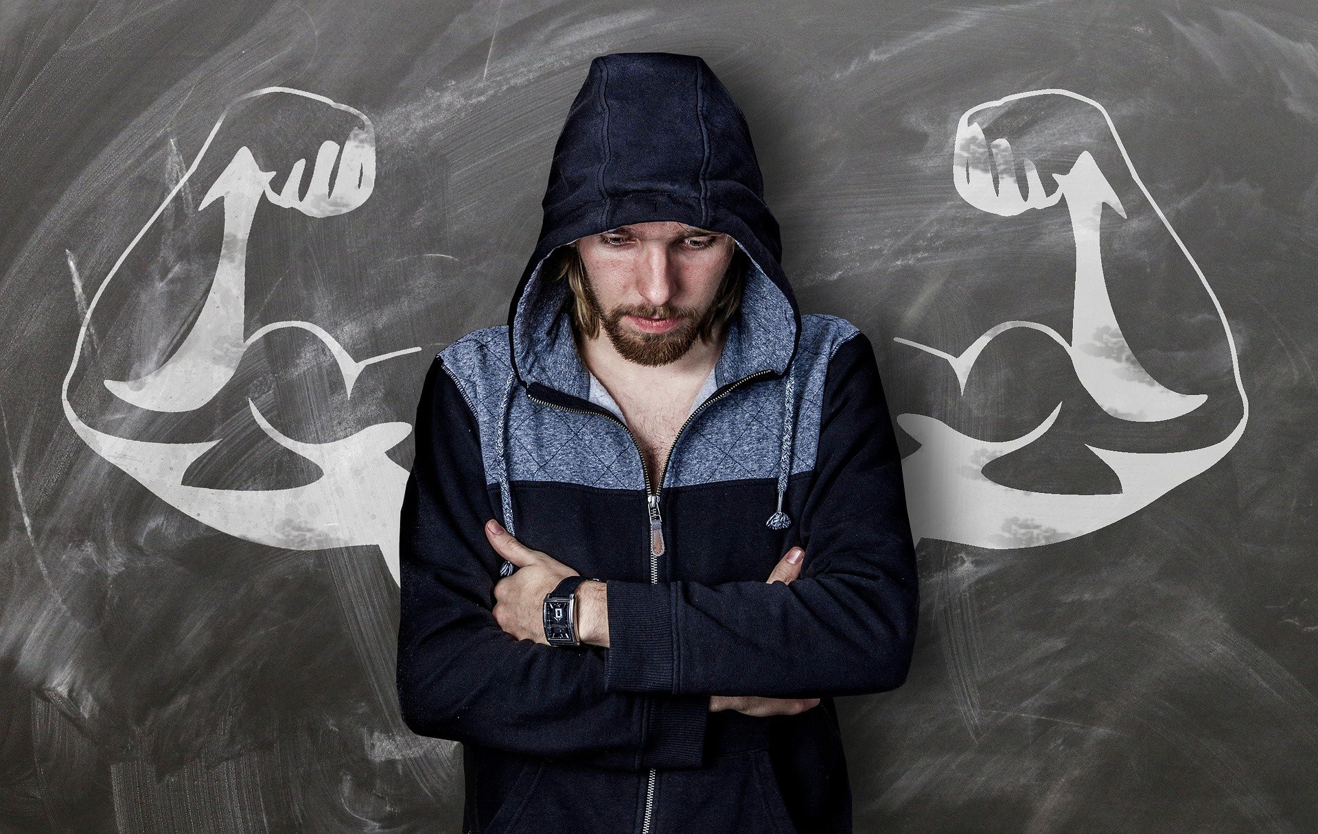 Man standing with arms crossed in front of a drawing of muscular arms flexing. It looks like his arms are the strong ones.