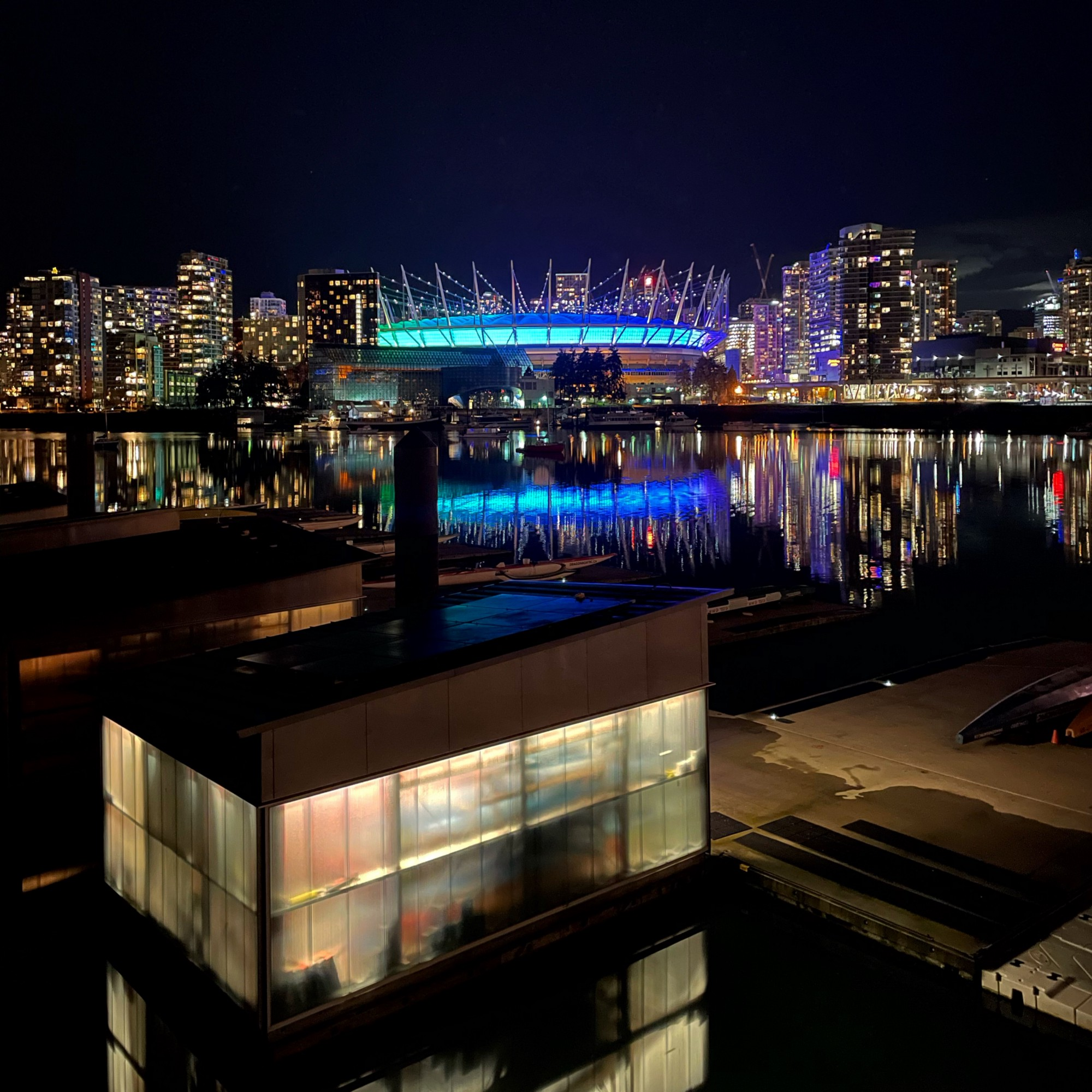 A cityscape at night, showing a lit stadium, hi-rises, and a body of water