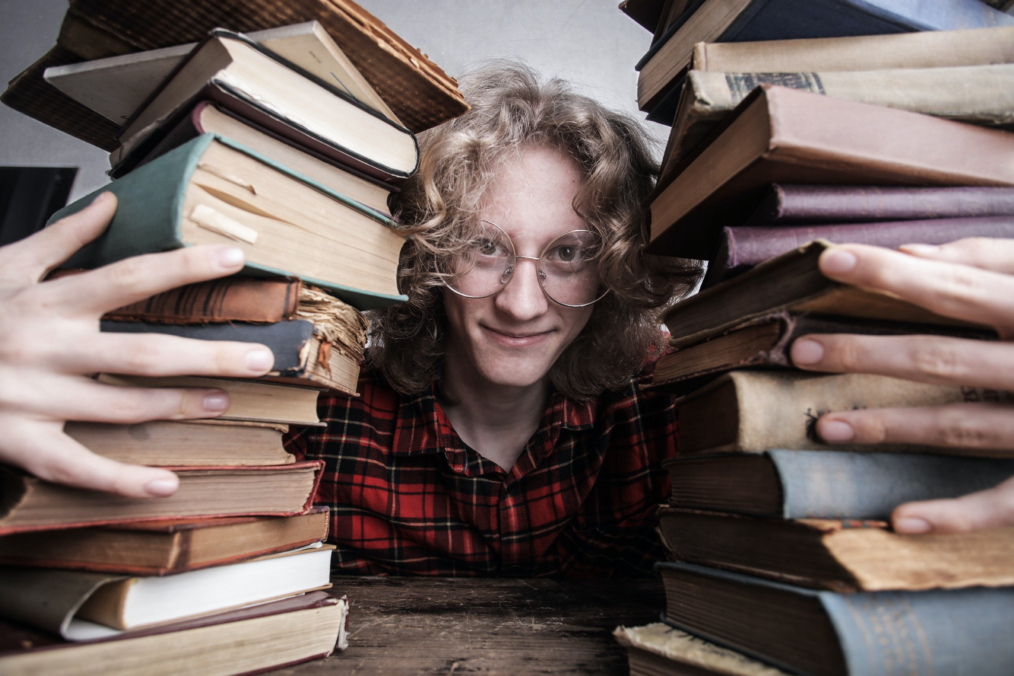 A person looking through two piles of books