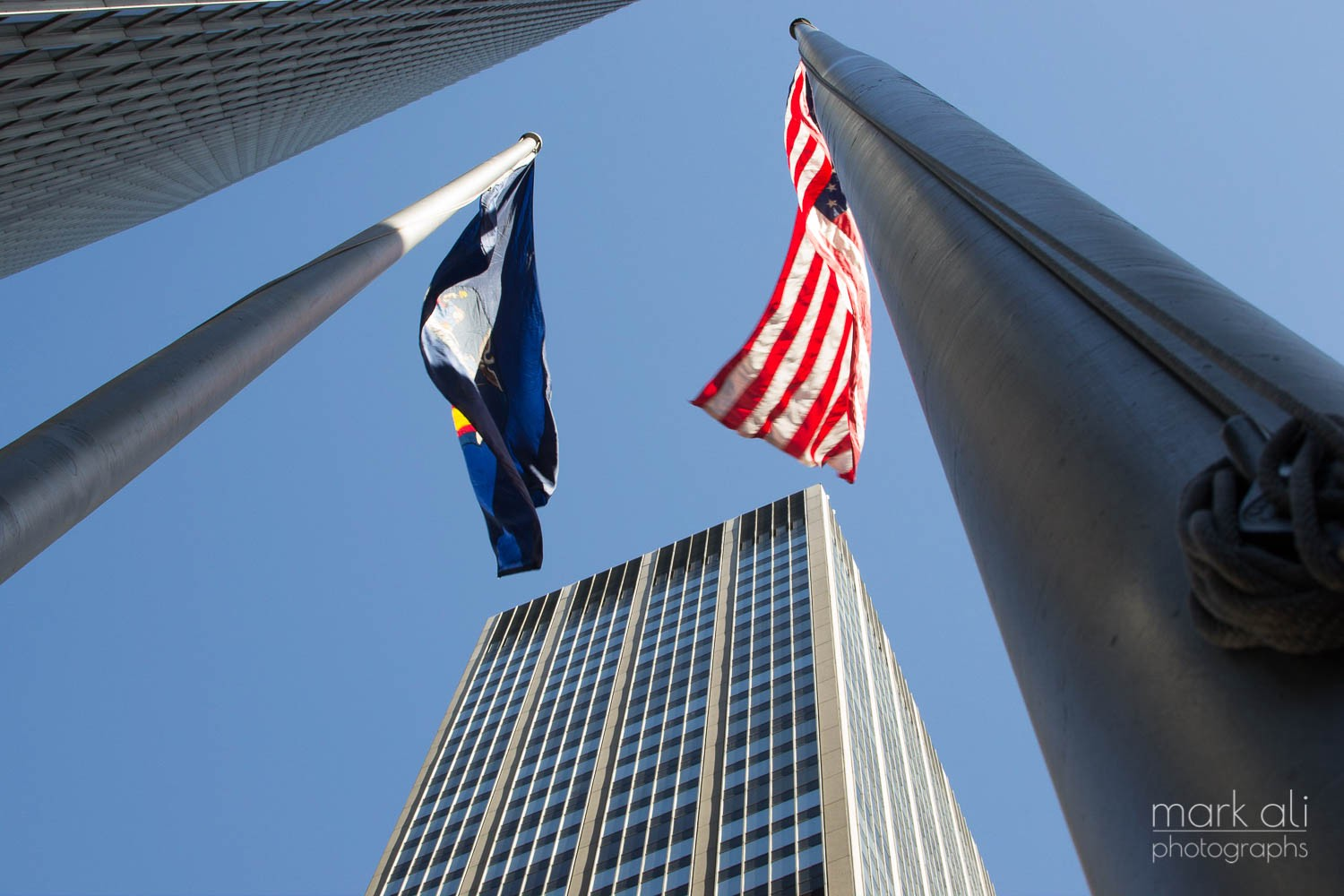 A shot looking up at flag poles and skyscrapers in Manhattan.