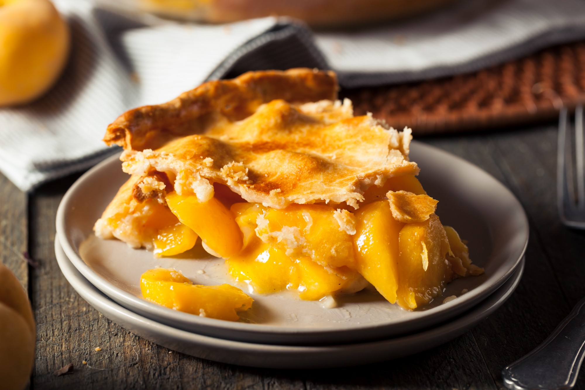 A slice of peach pie on a plate on a table made of dark wood.
