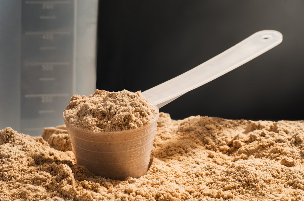 Heap of whey protein powder with measuring scoop