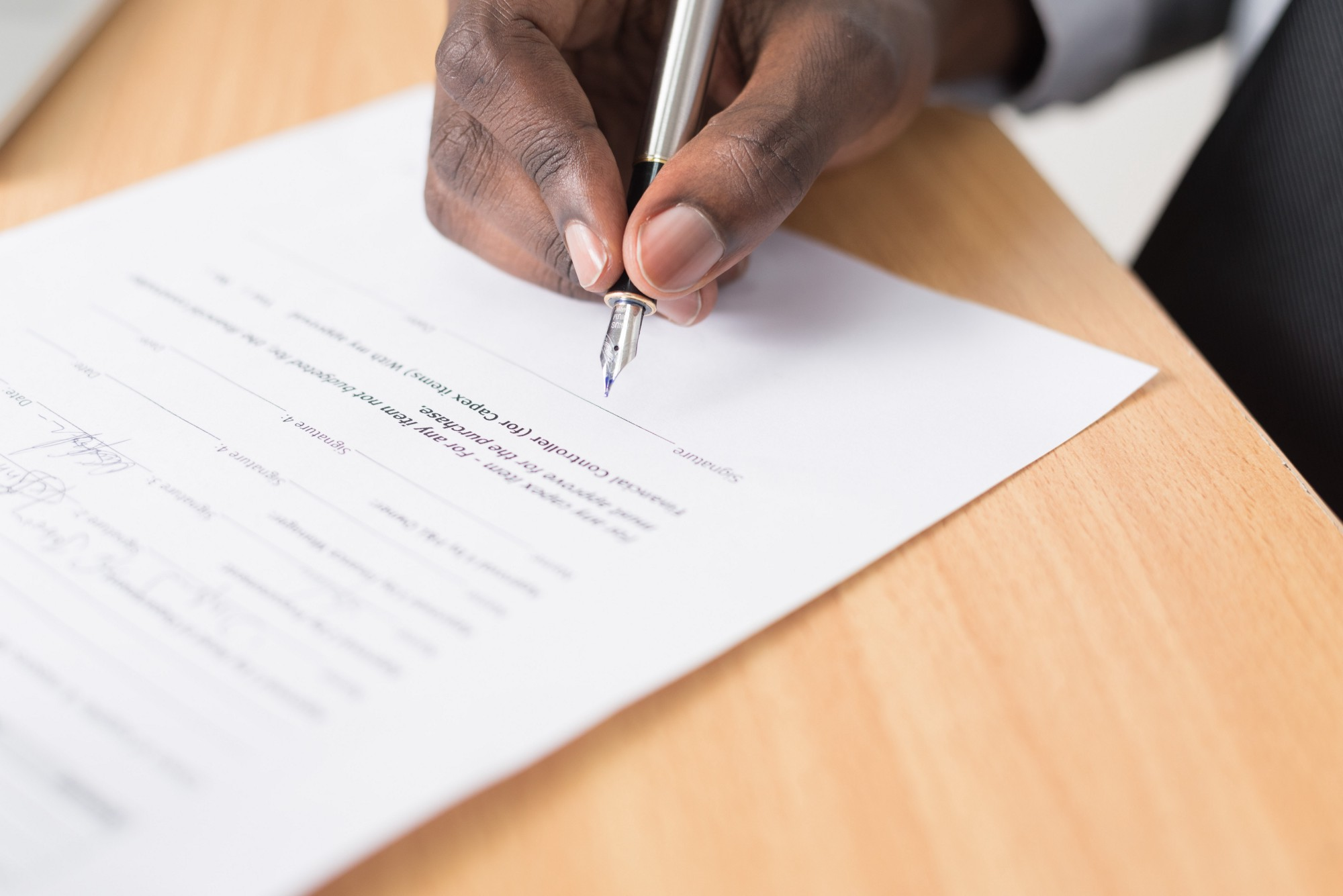 Person signing a paper contract