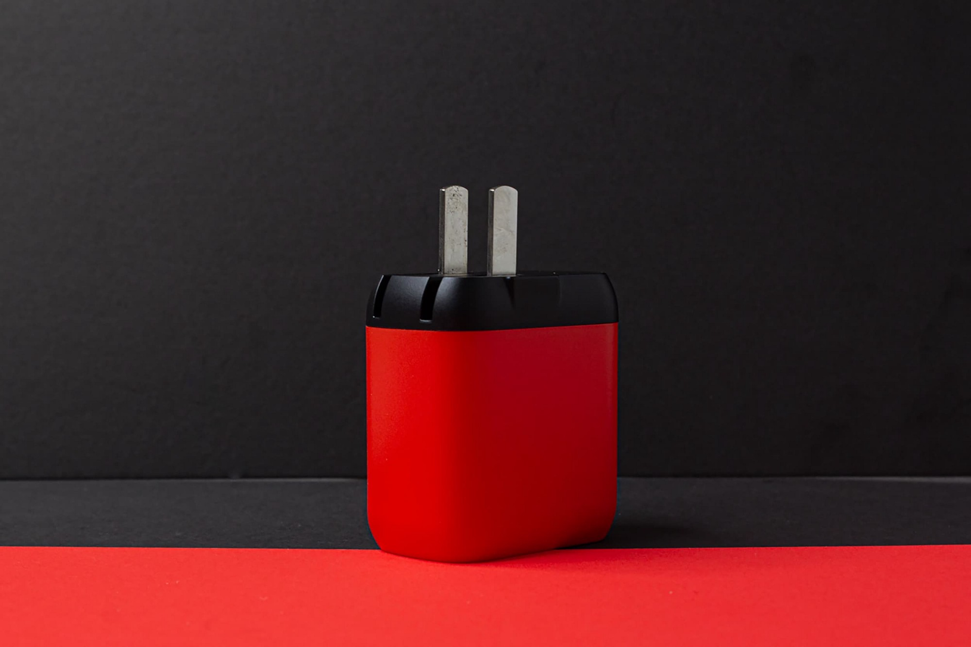 A red, and black coloured plug, sat on a black table