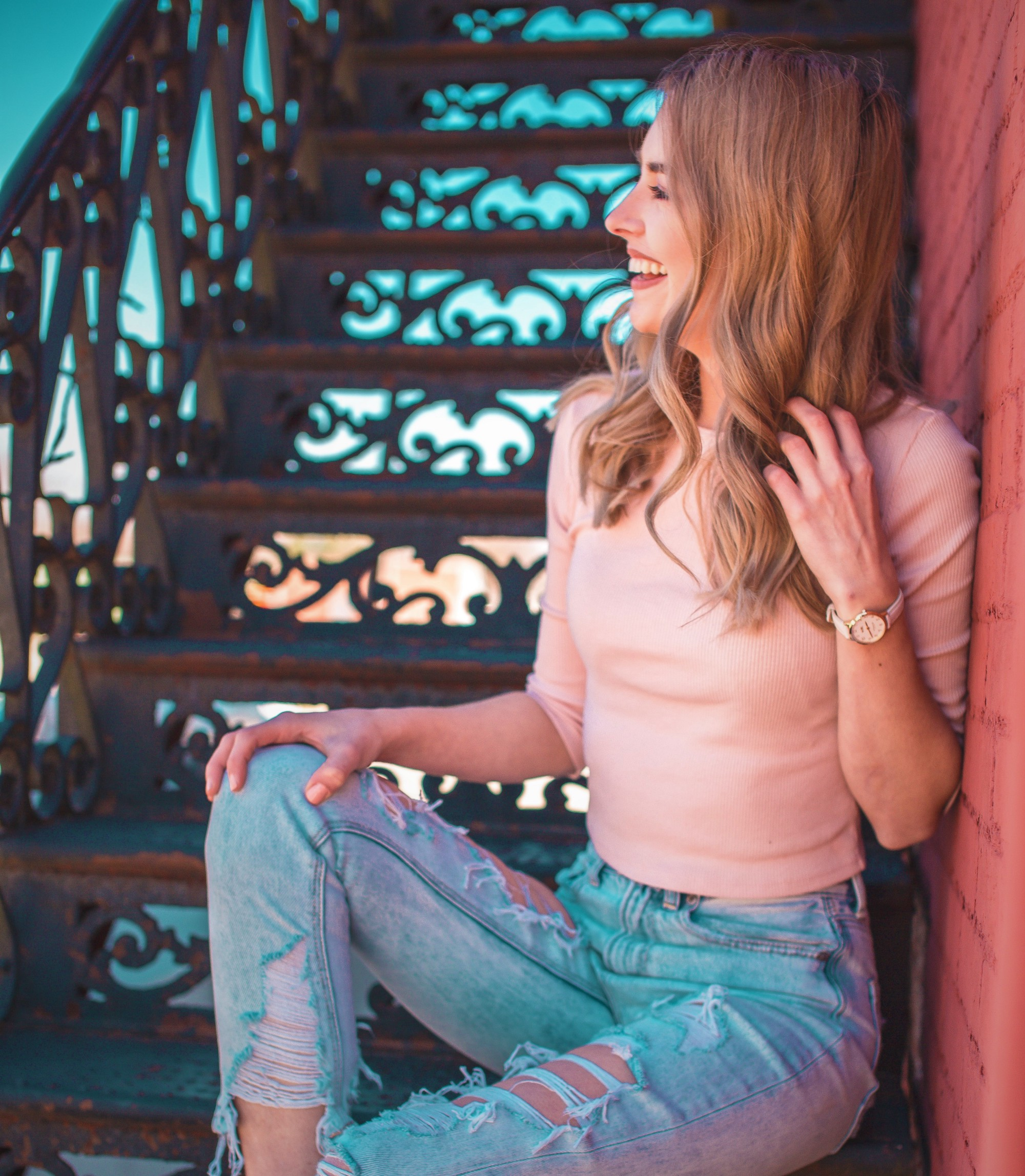 smiling girl with long brown hair wearing pink top and torn blue jeans