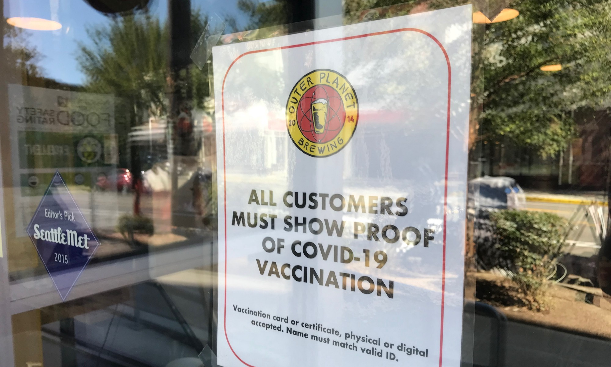 Sign on window at brewery advising patrons of COVID-19 vaccination requirement.