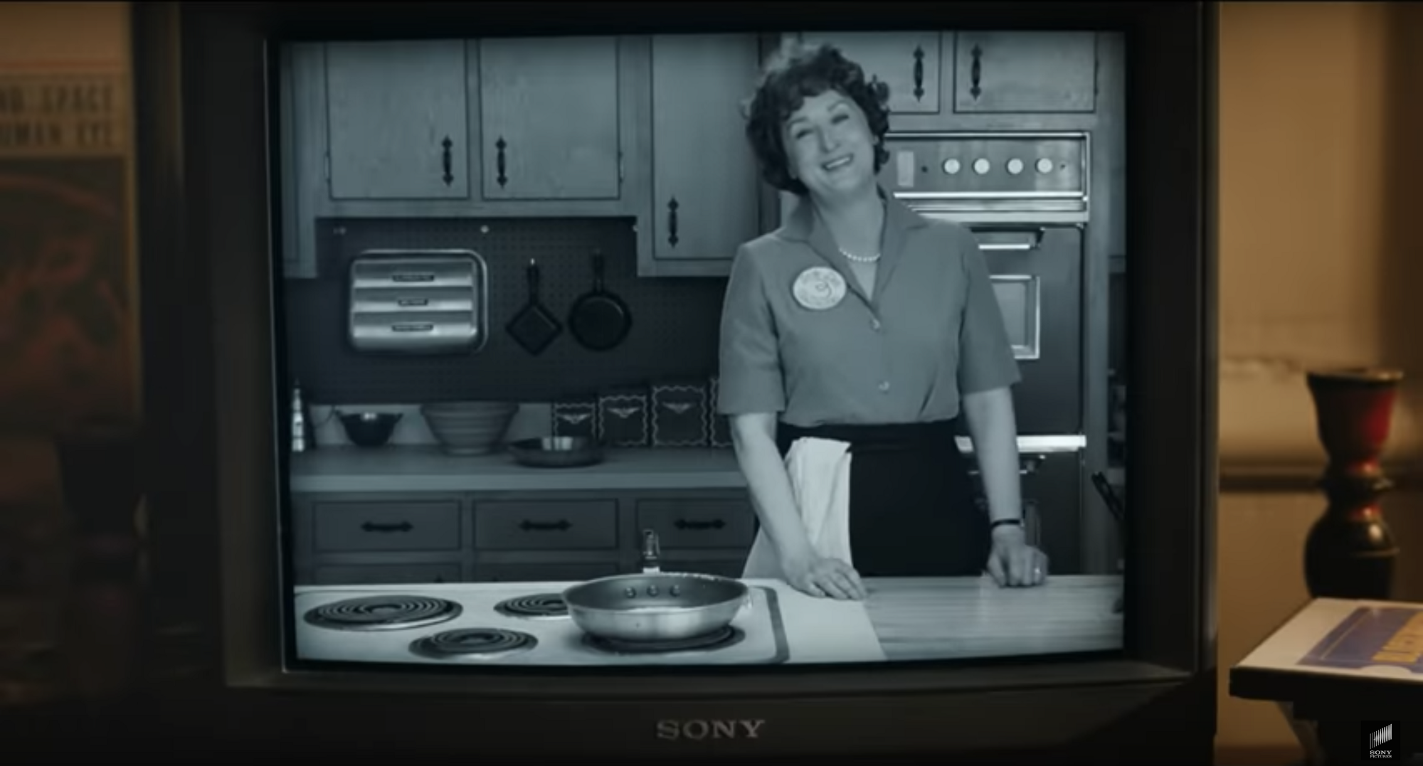 Meryl Streep as Julia Child on her cooking show, smiling in the kitchen