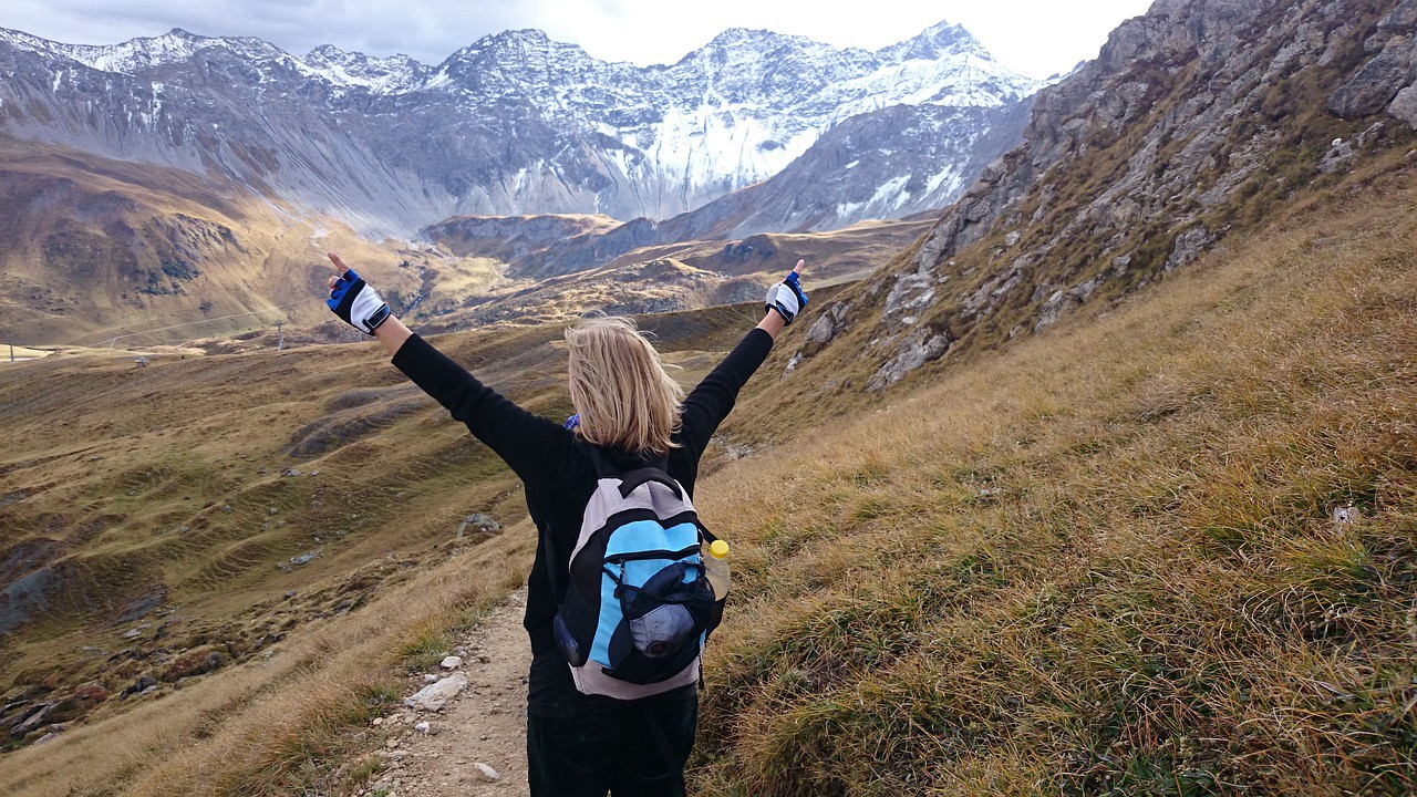 A woman with her arms raised on a trail headed towards a mountain range.