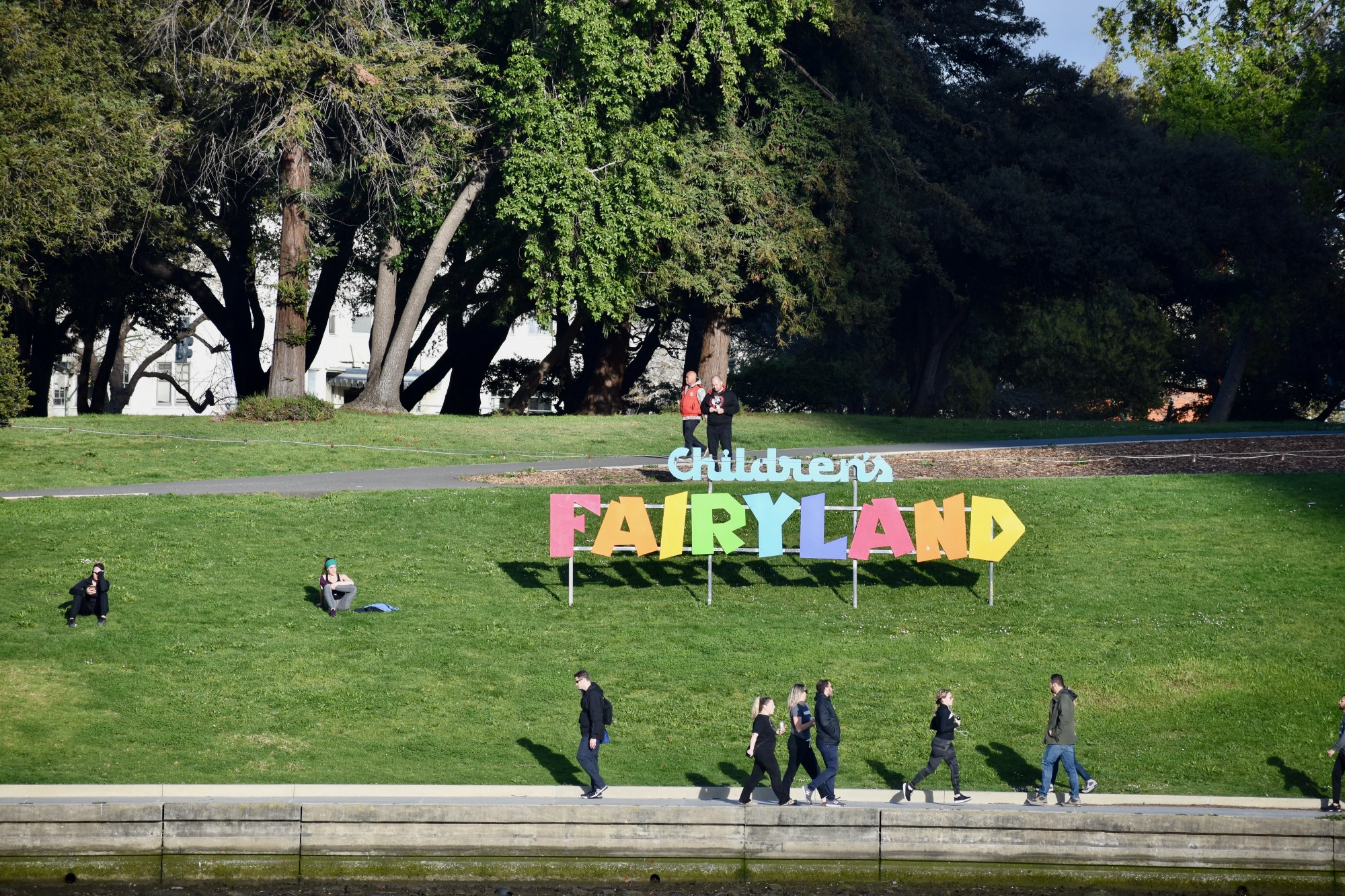 People walking under the big Children's Fairyland sign.