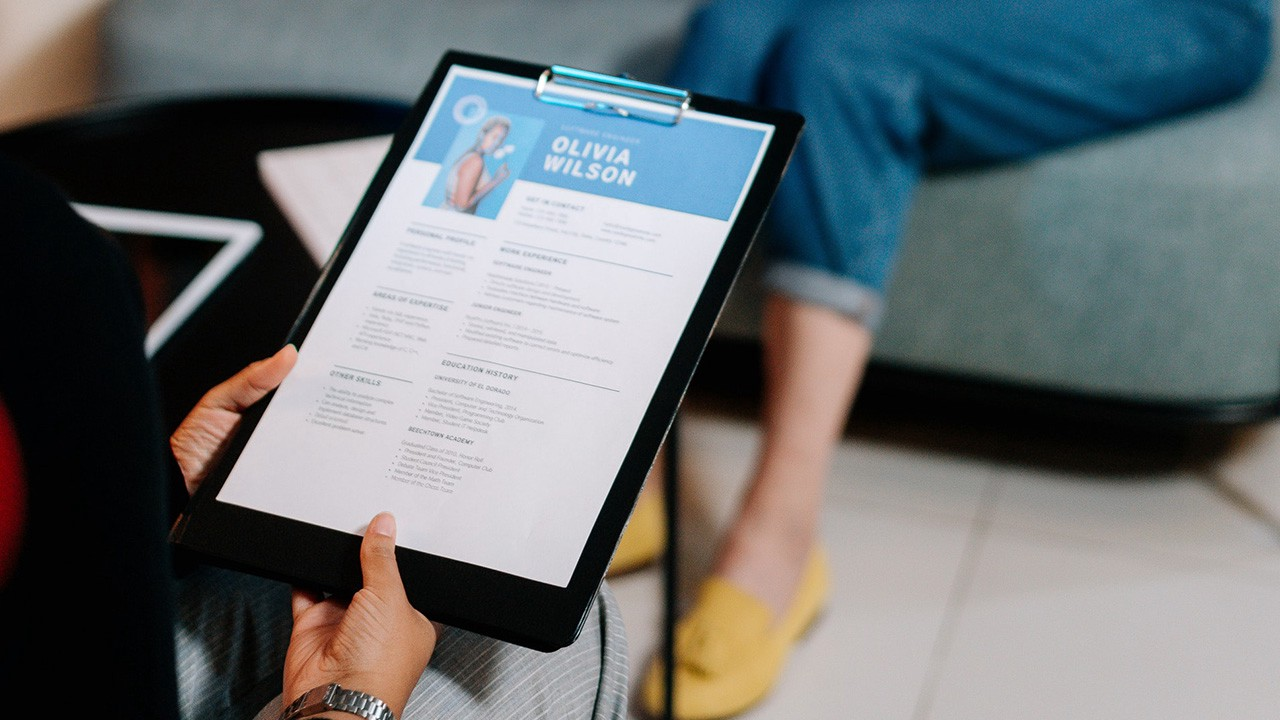 A woman holding a clipboard with her resume.