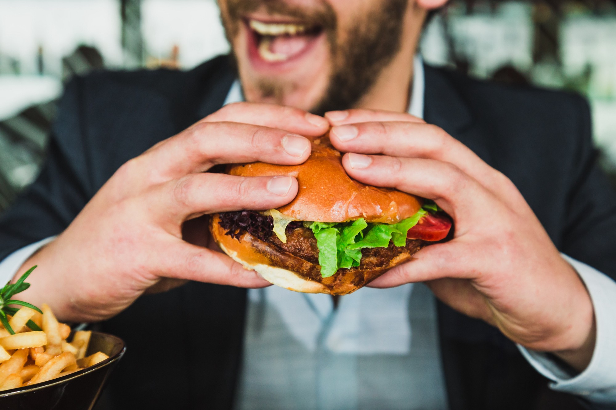 A well-dressed man holds a hamburger, about to chew. He is smiling. The burger is probably not synthetic meat.