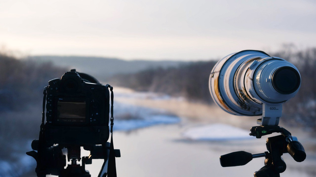 Two cameras pointing at a snowy lake as the sun is setting.
