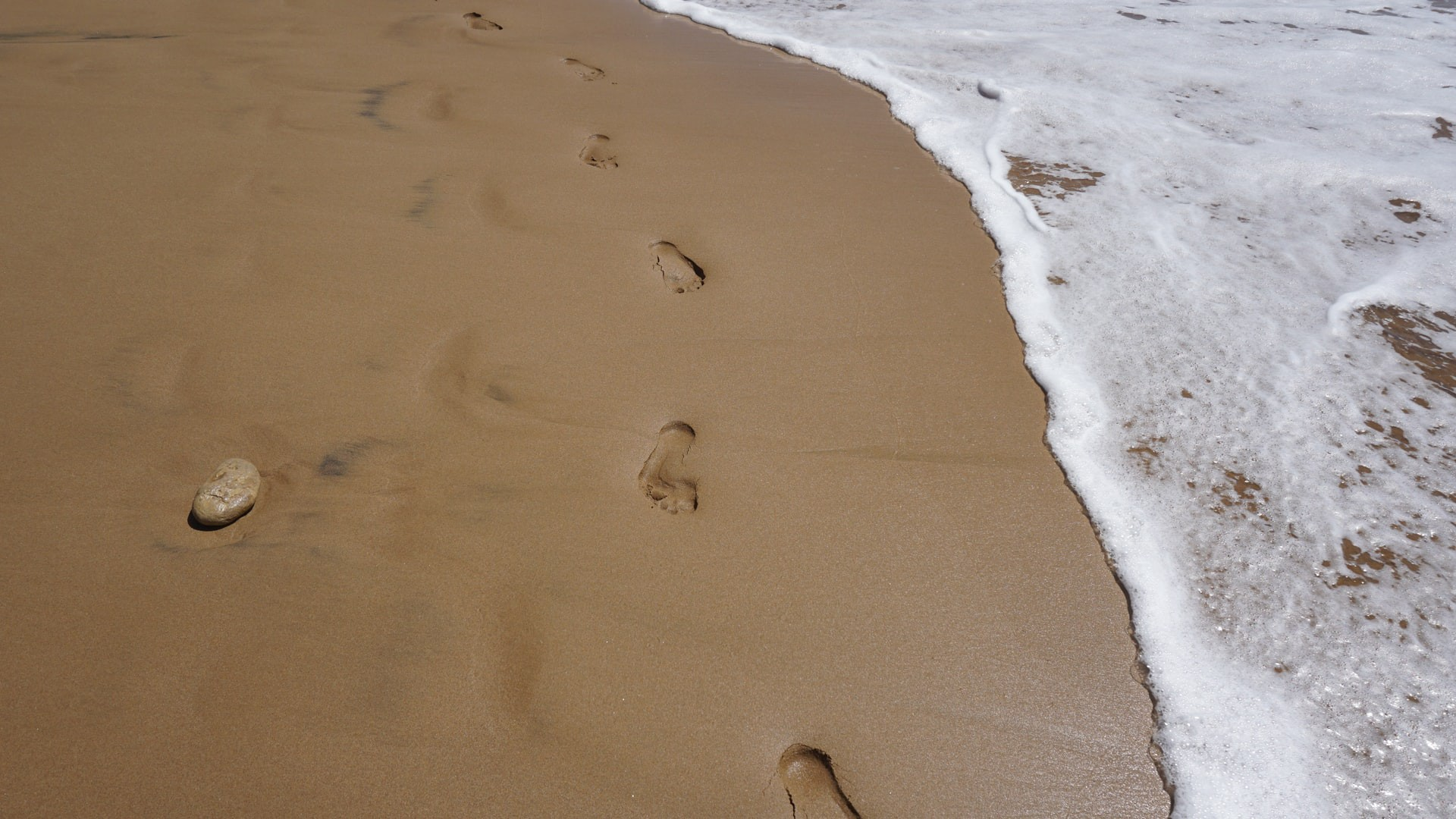 Colour photograph is human barefoot footprints in wet sand at the beach next to the incoming tide.