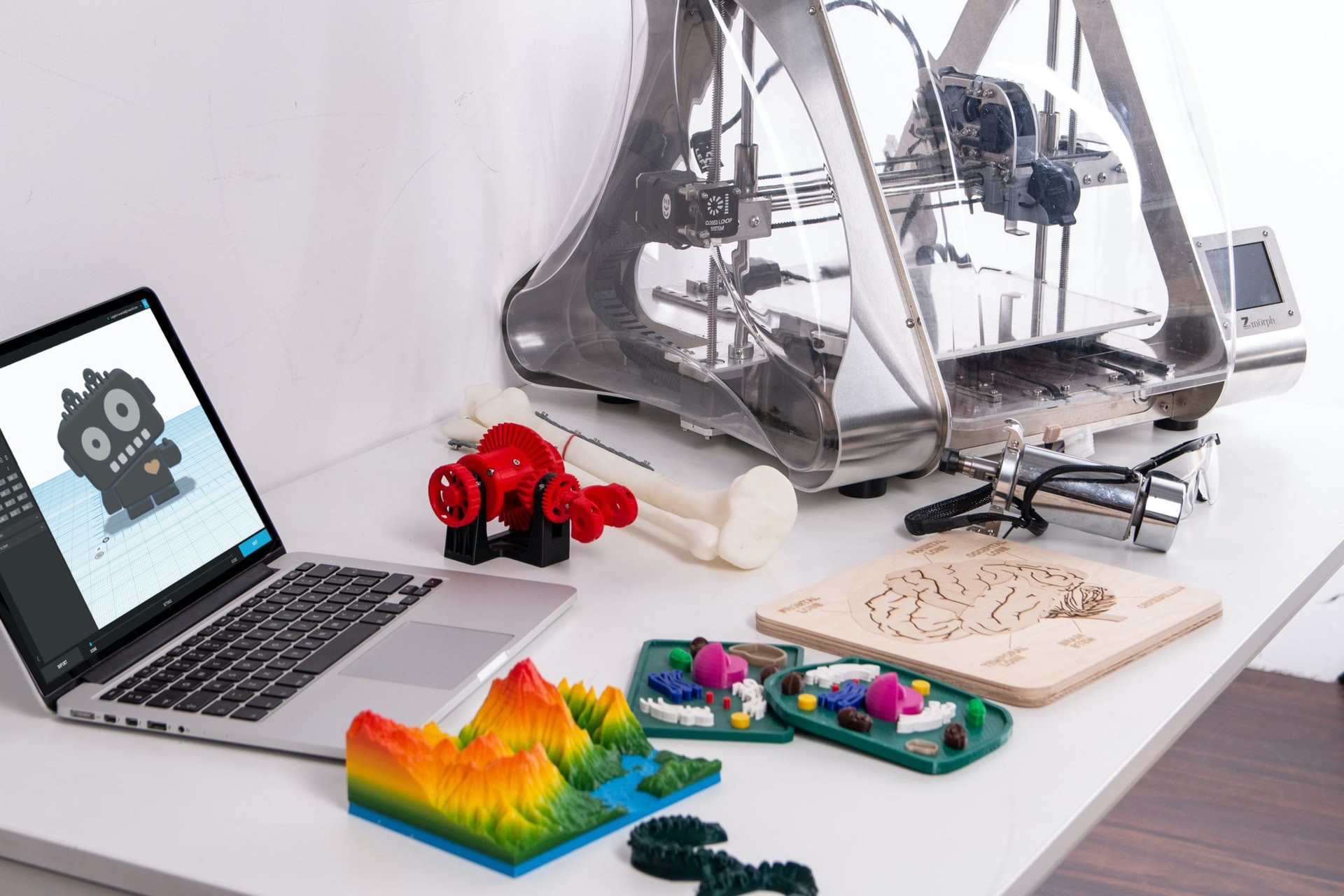 A 3D printing machine next to a laptop and 3D printed objects.