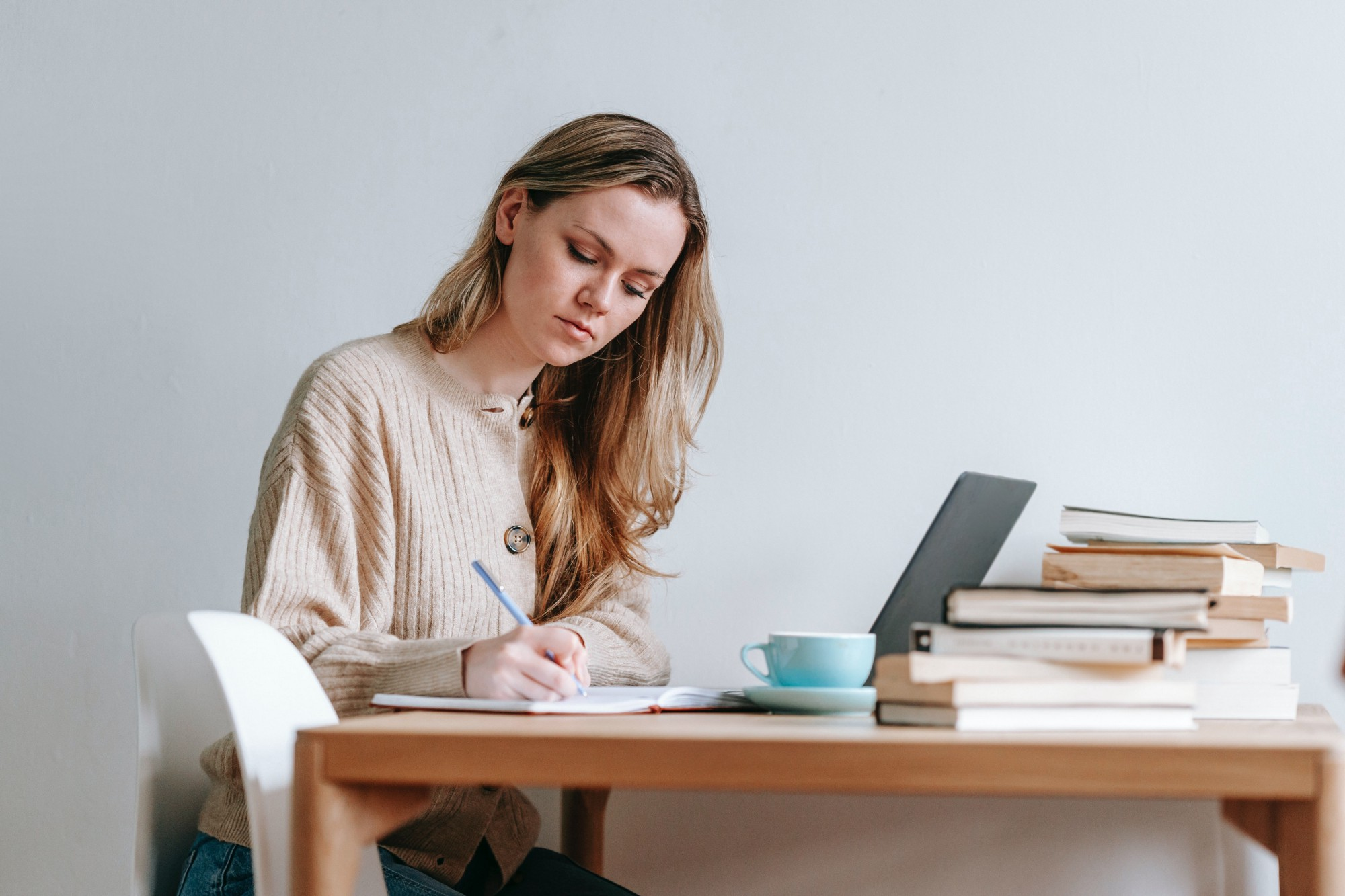 photo of woman writing with lots of books on her desk