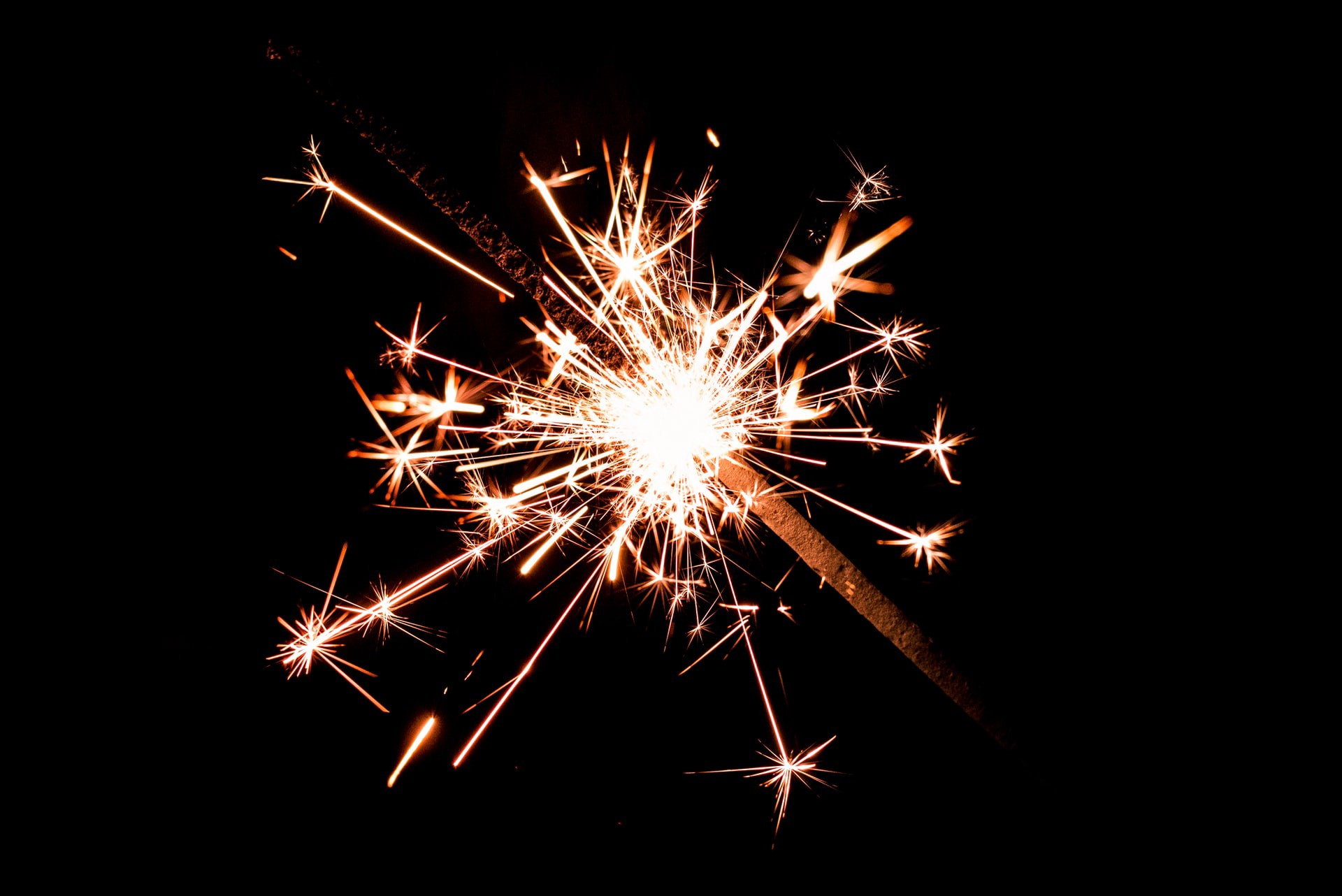 Alt: colour macro photograph of a sparkler burning bright against a dark background. Image credit: Jez Timms | Unsplash