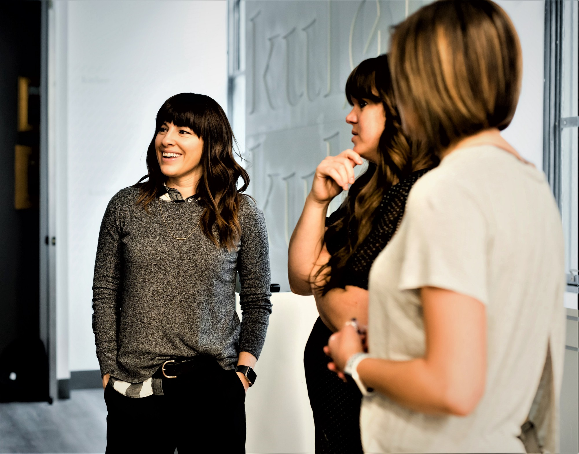 Three girls standing in hallway talking one with hands in pocket smiling