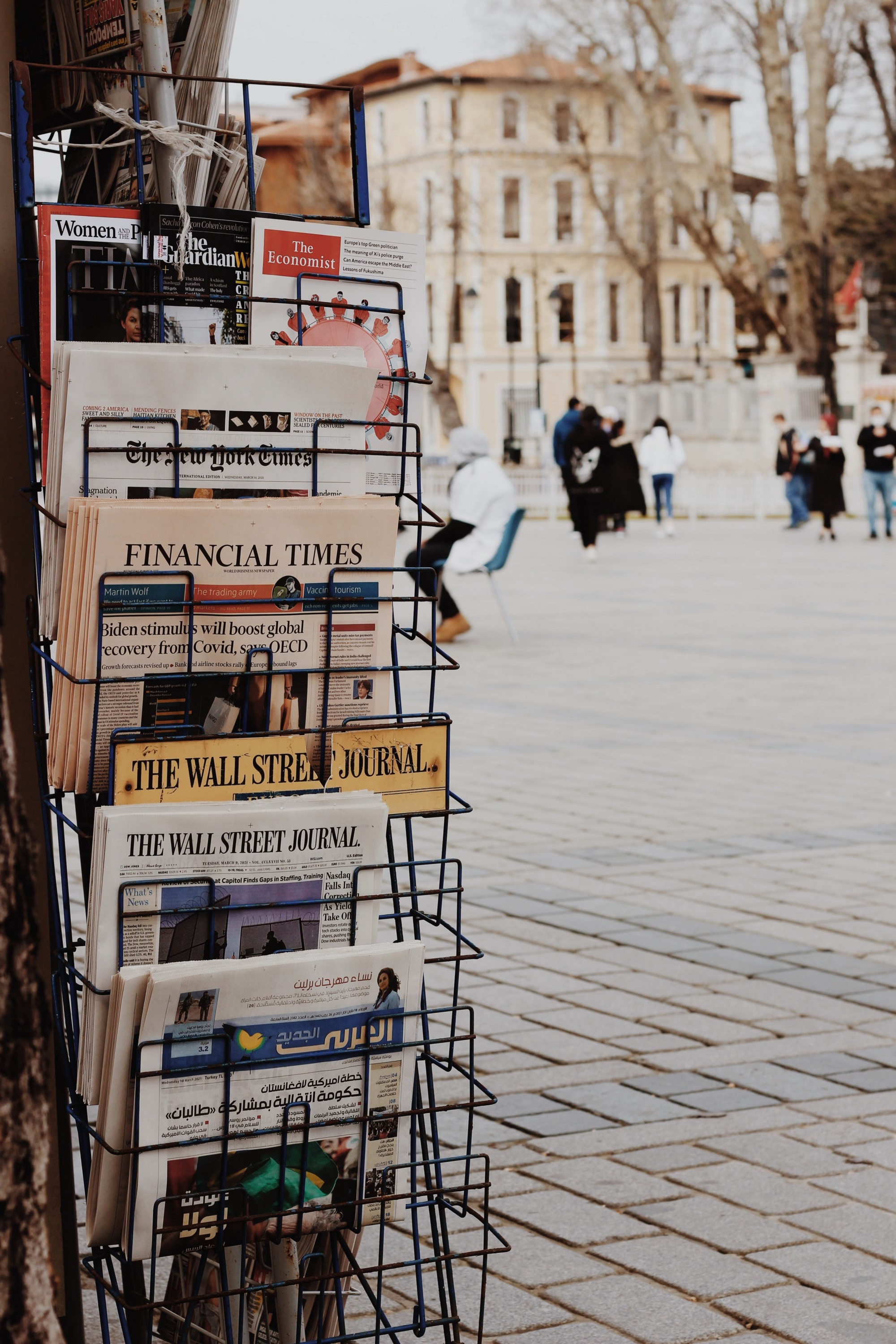 Newspaper vendor stand in a open square with newspapers in the rack.
