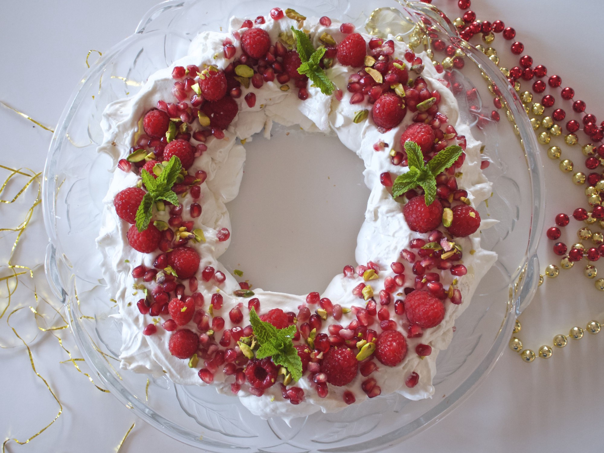 A wreath made of stiff sweet white vegan meringue sits on a plate and is decorated with red berries and leaves