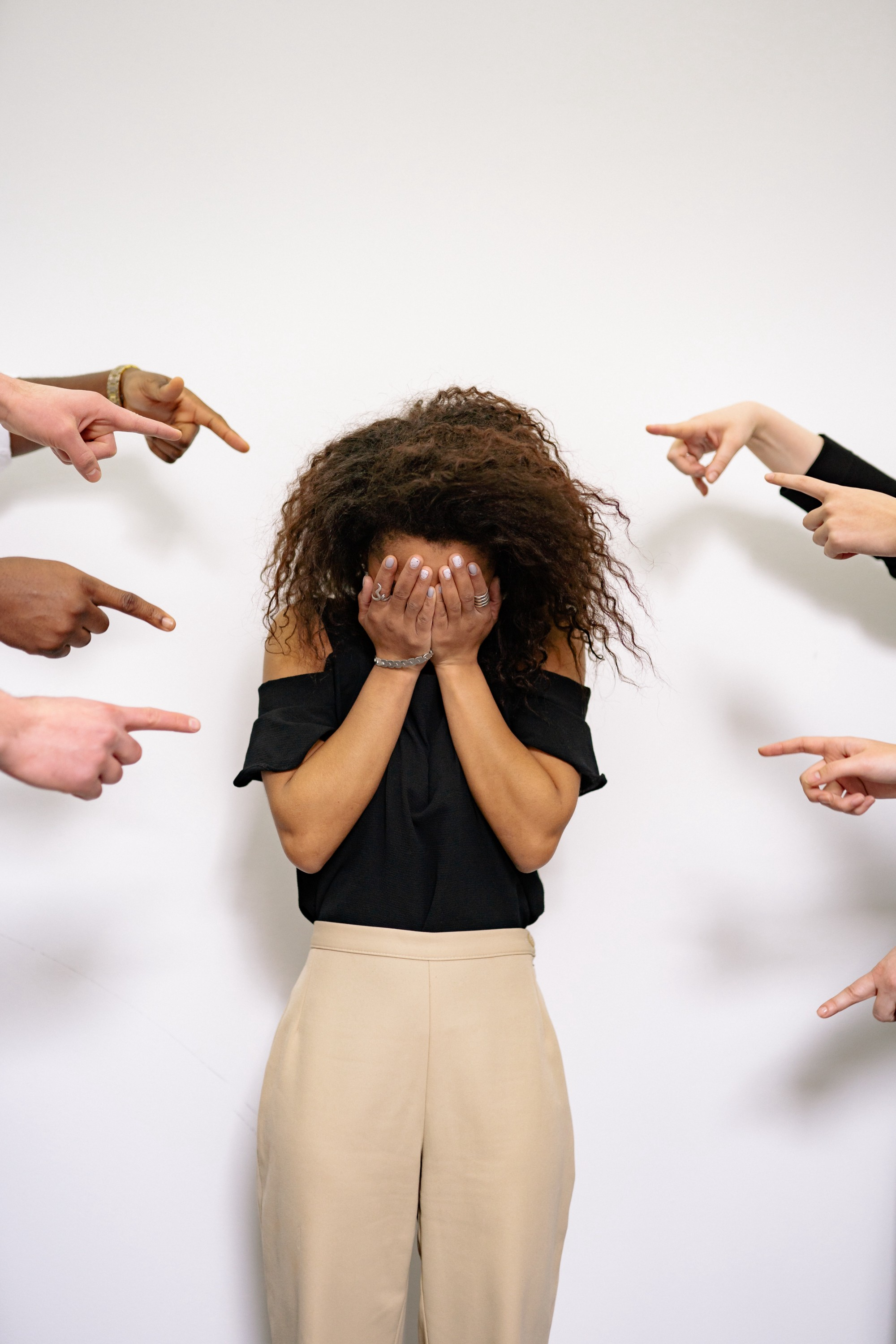 A woman of color covering her face with several people pointing fingers at her.