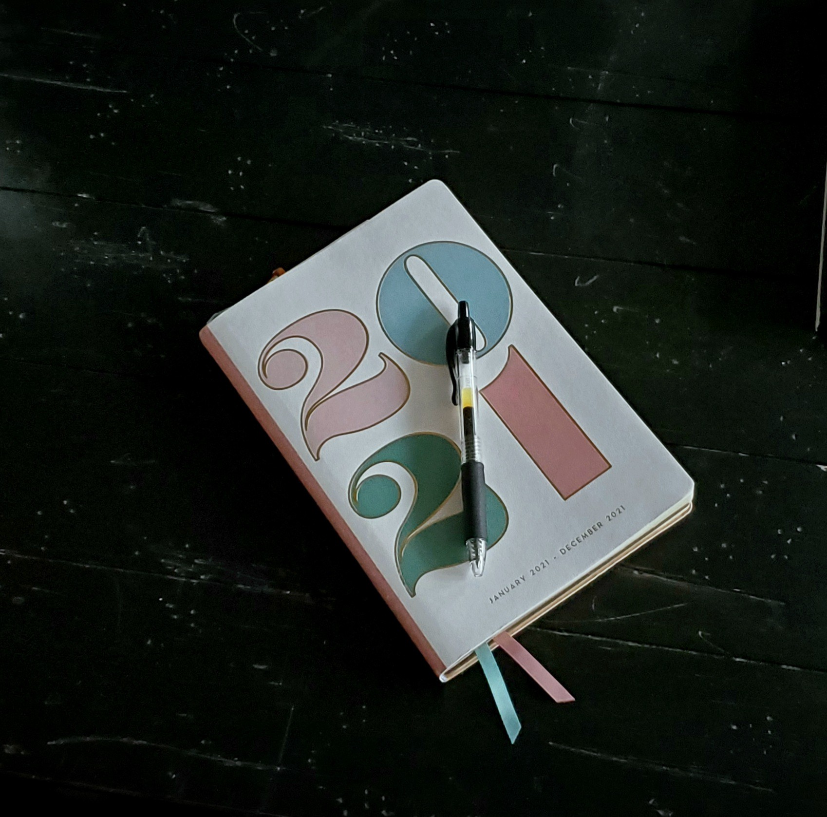 white, pink, blue and green 2021 calendar with black wood background. Black pen on top.