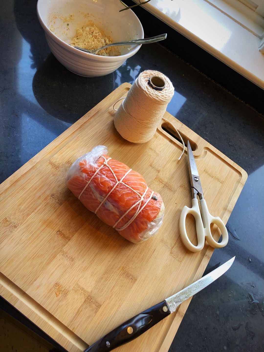 A trussed and wrapped salmon roll sits on a cutting board alongside some kitchen shears and butcher's twine