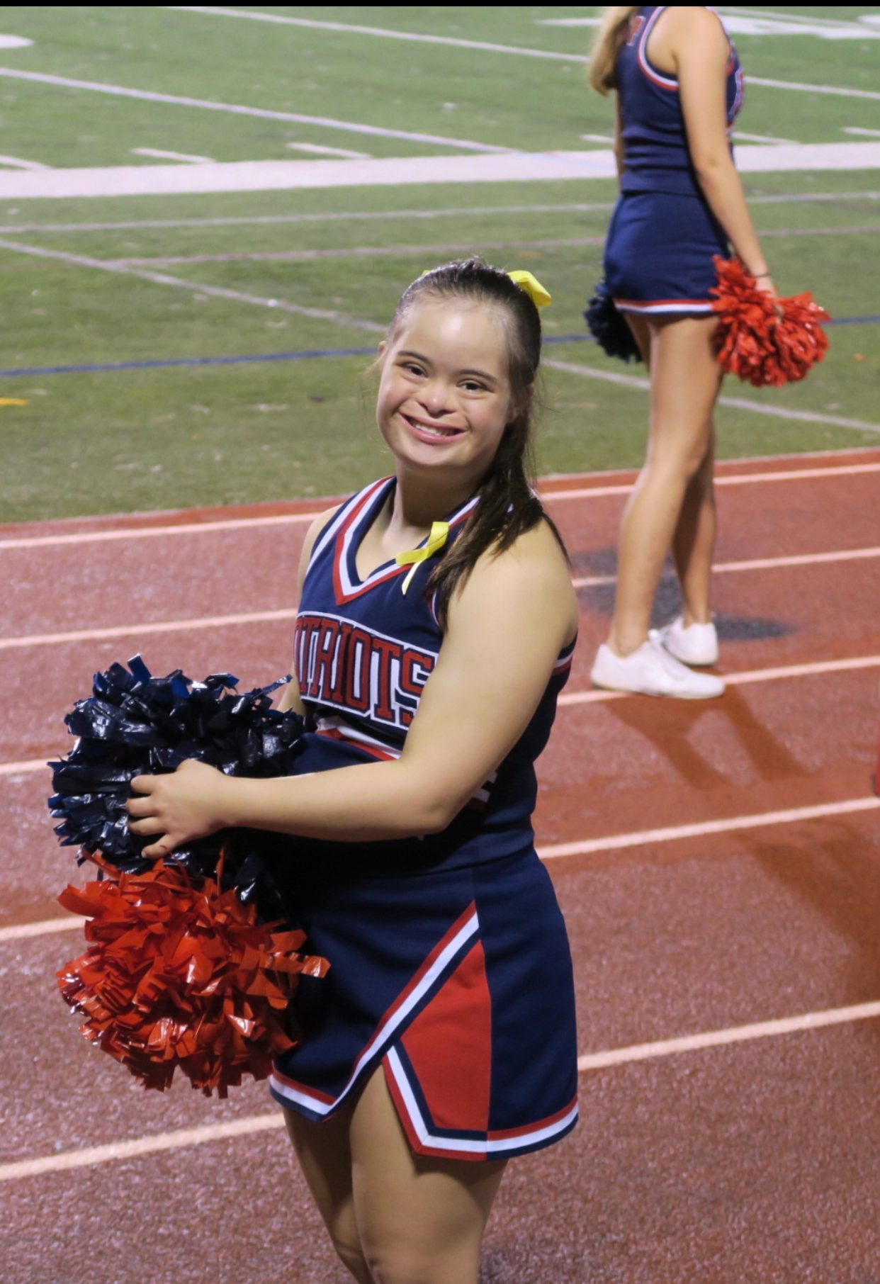 Picture of Saris Marie in her cheerleading uniform. She is standing on her school's track with pom-poms in her hand.