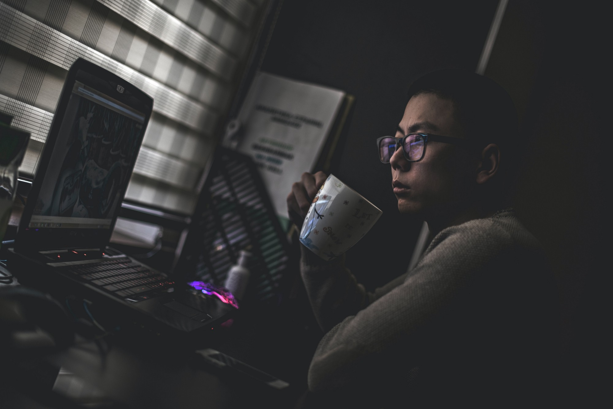 Person holding mug while looking at laptop