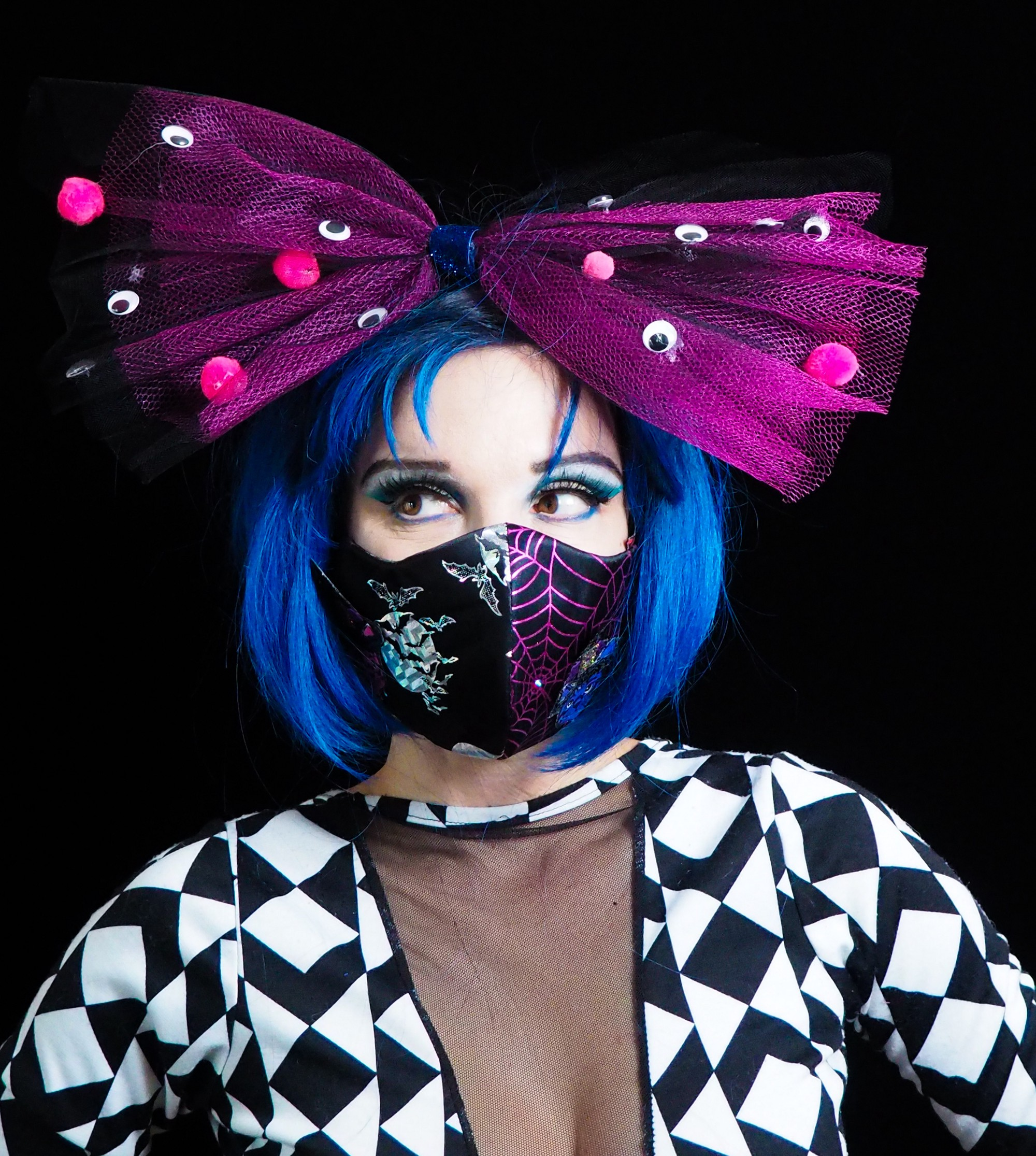 A person with a blue bob haircut wearing a huge purple hairbow and a mask with shiny bats + moons and purple spiderwebs