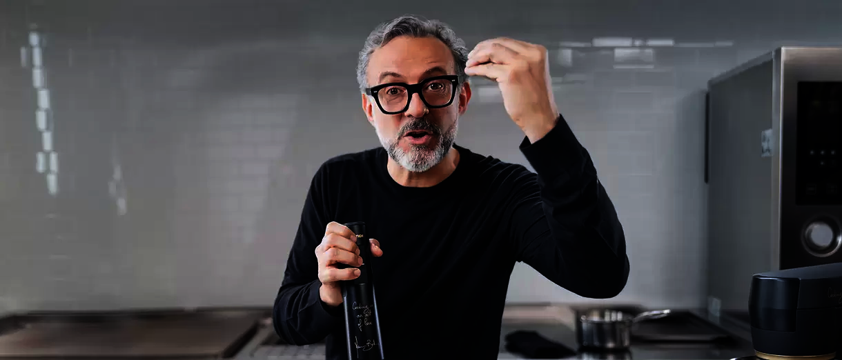 A person with short salt-and-pepper gray hair + matching facial hair and glasses talking, holding a glass bottle.